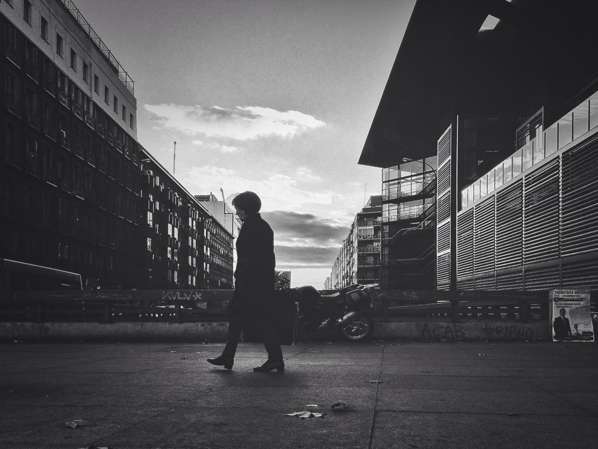 architecture, built structure, building exterior, full length, sky, lifestyles, walking, men, rear view, leisure activity, cloud - sky, person, city, standing, cloud, city life, street, silhouette