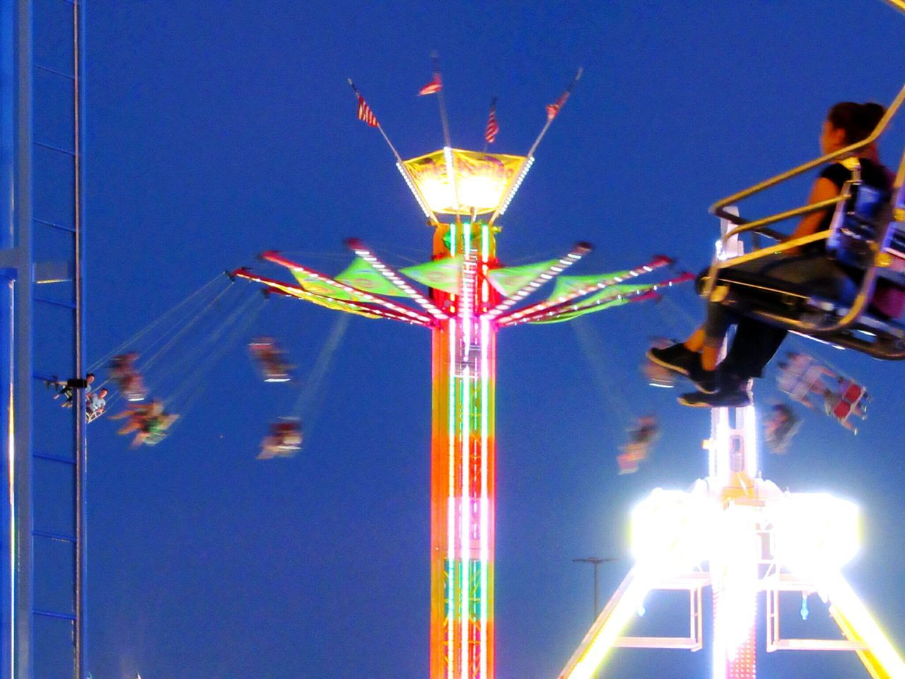 arts culture and entertainment, amusement park, low angle view, illuminated, amusement park ride, night, motion, clear sky, outdoors, blue, no people, multi colored, sky, carousel