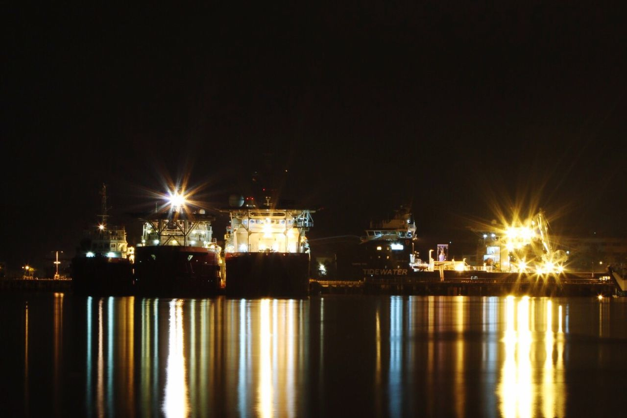 Illuminated Dockyard Reflecting In Water