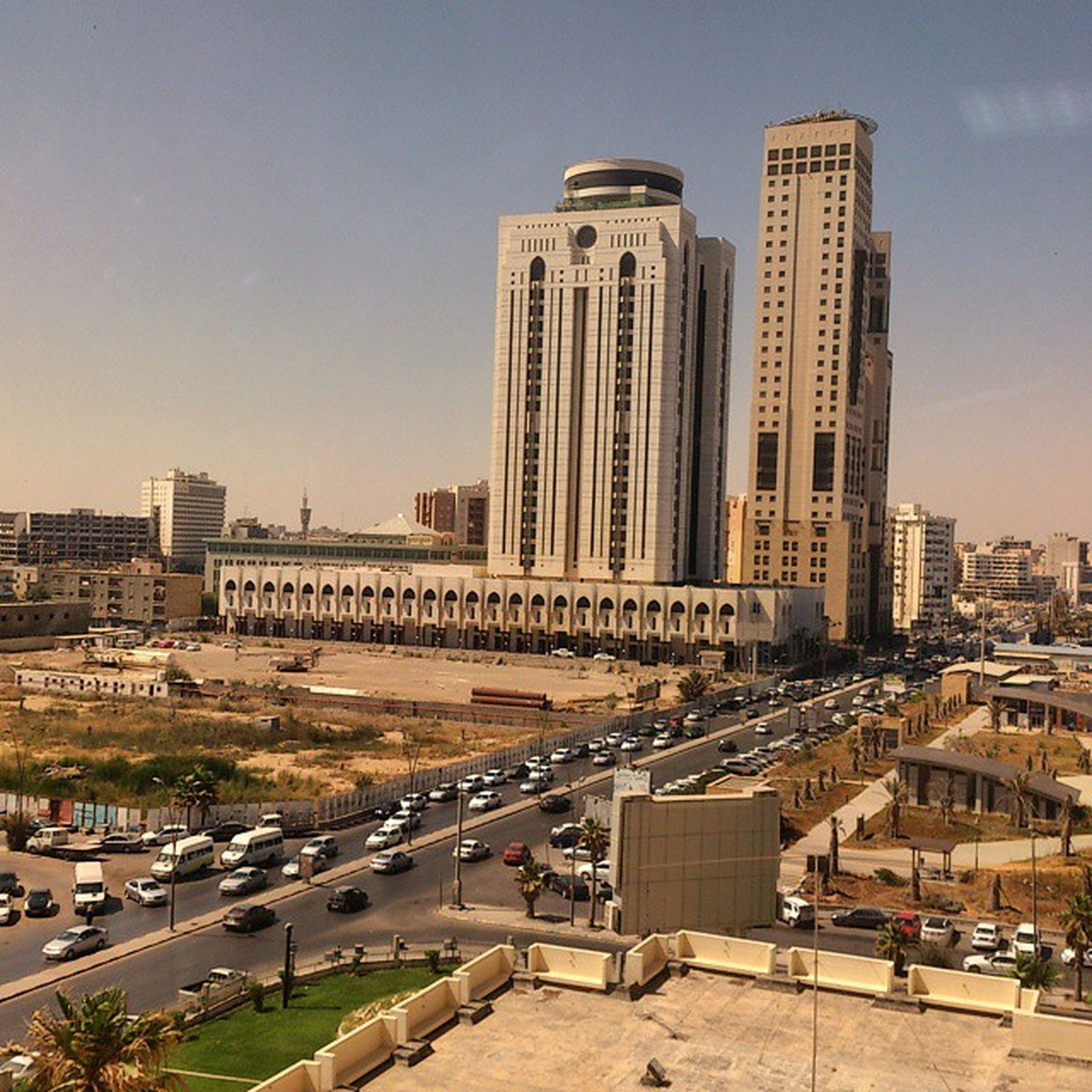 architecture, building exterior, built structure, city, transportation, car, land vehicle, road, street, city life, mode of transport, tower, cityscape, high angle view, sky, clear sky, tall - high, incidental people, skyscraper, city street