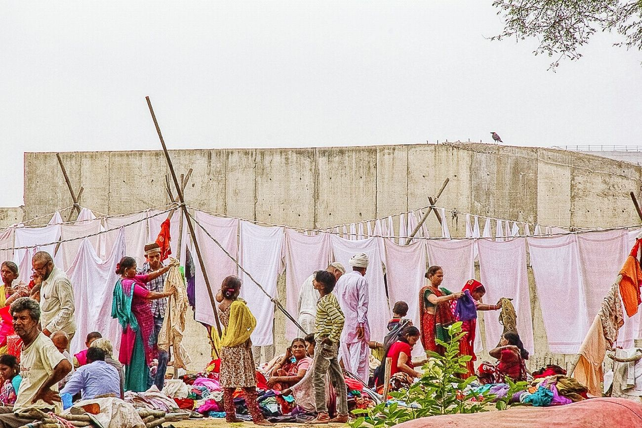 South location , Busy Market In Front and Washhouse at back. People Watching Clothes for Purchase , Big Wall Background make it dramatic and bird on top of the wall make it calm