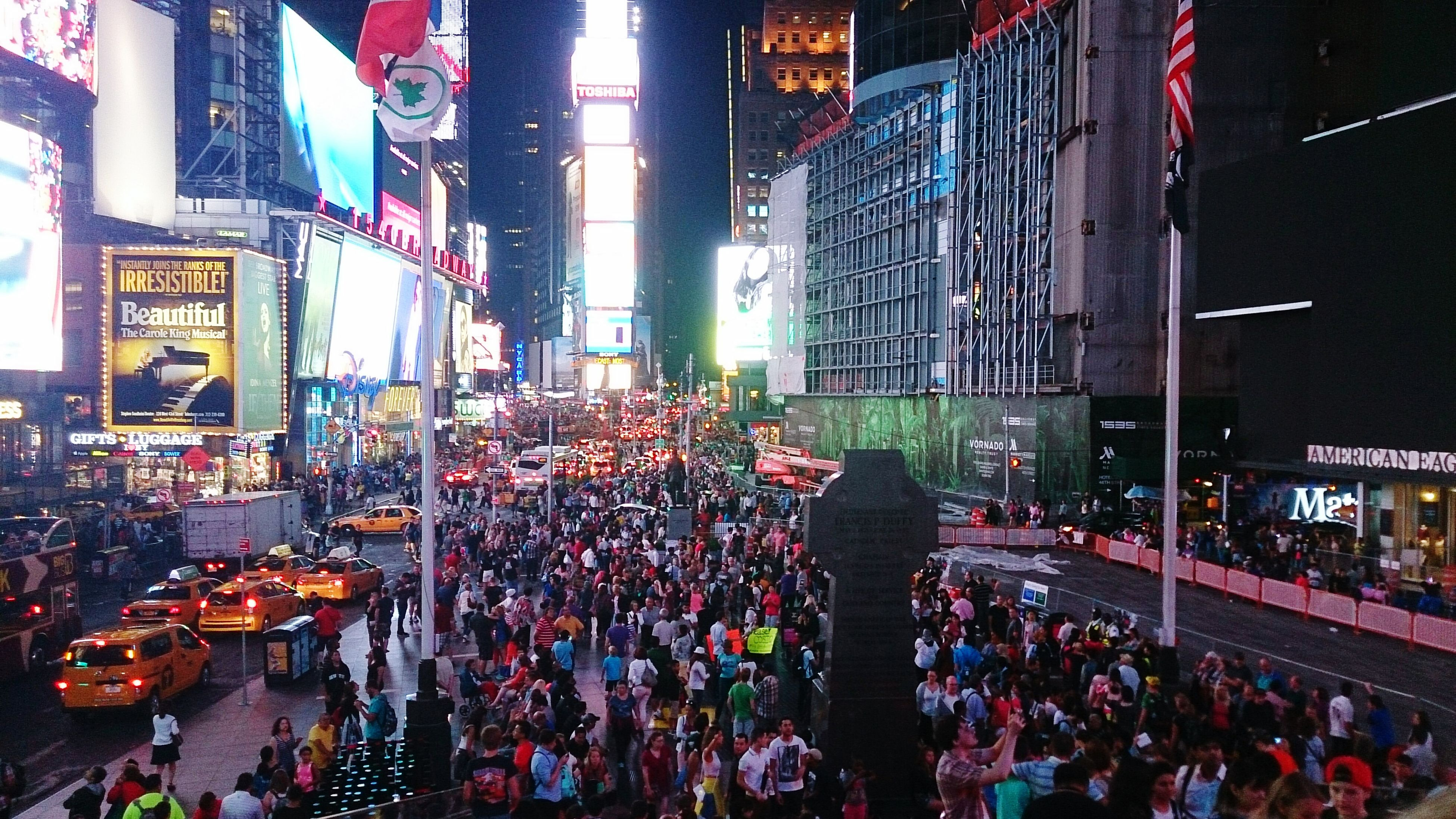 large group of people, crowd, illuminated, city, street, building exterior, night, city life, person, built structure, architecture, men, lifestyles, market, leisure activity, mixed age range, city street, celebration, high angle view