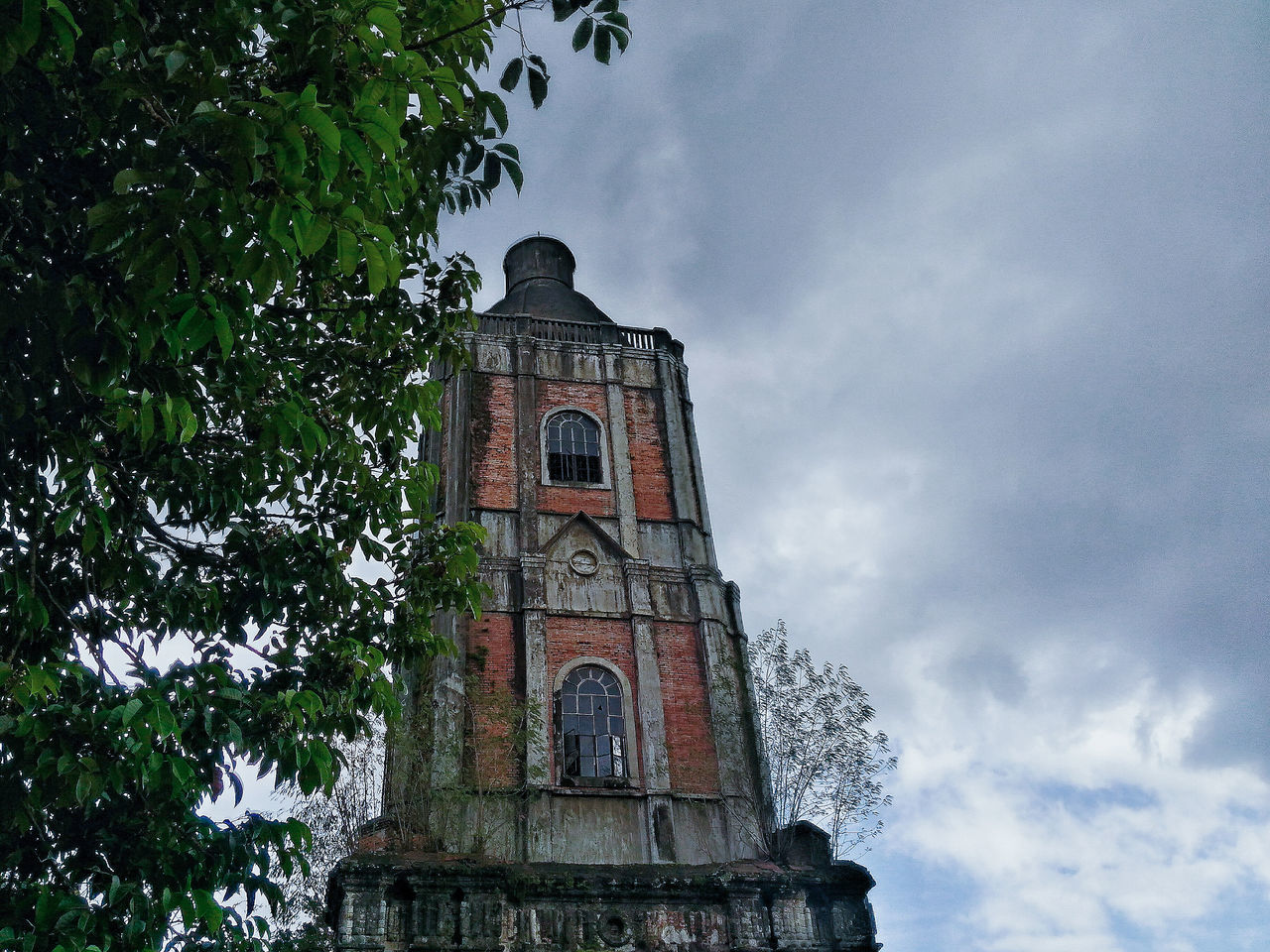 religion, sky, place of worship, spirituality, architecture, cloud - sky, low angle view, tree, history, day, no people, outdoors, built structure, bell tower, building exterior, clock tower, nature