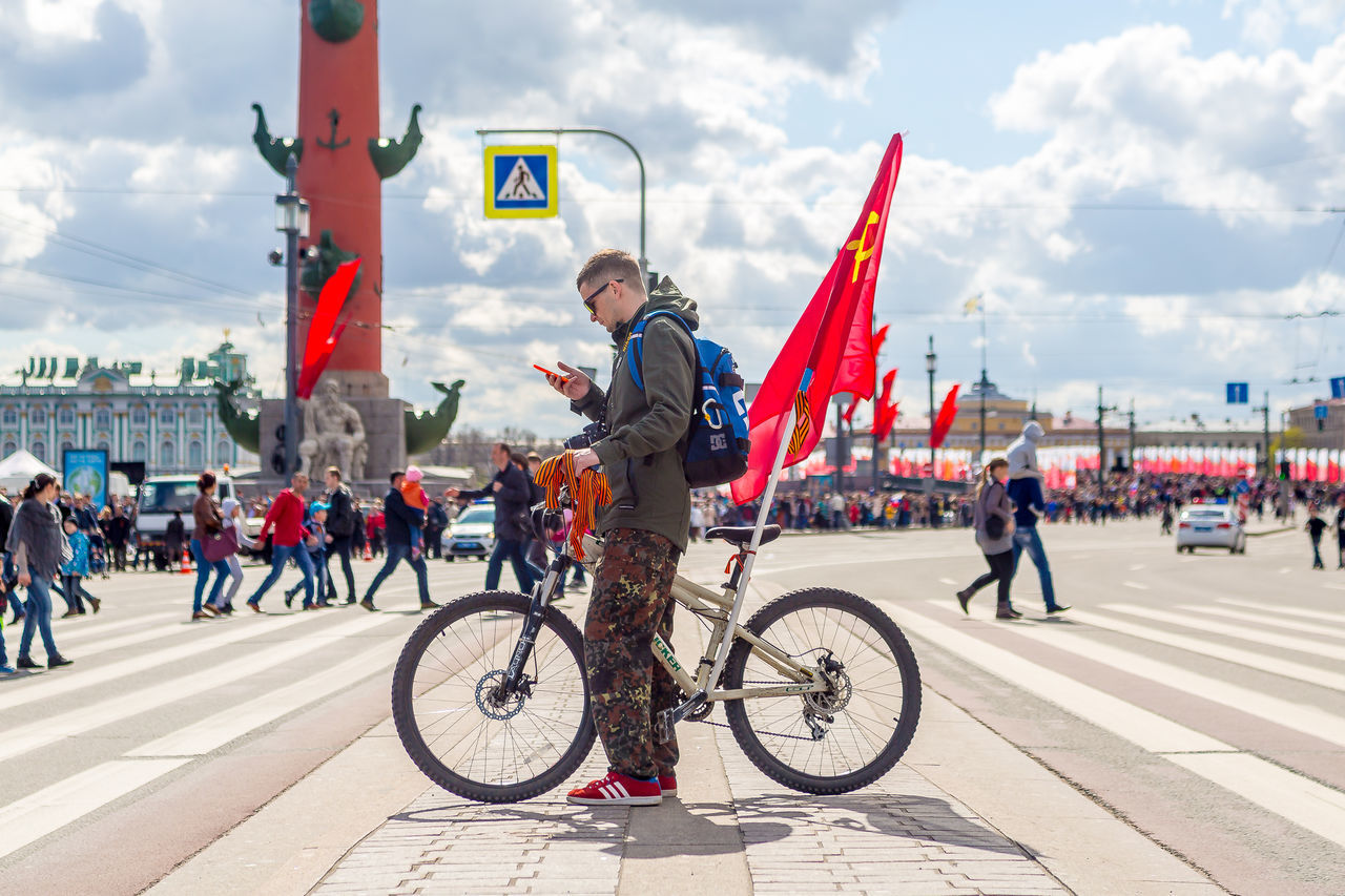 bicycle, transportation, mode of transport, land vehicle, real people, day, cycling, cloud - sky, sky, outdoors, flag, riding, lifestyles, city, helmet, built structure, cycling helmet, building exterior, men, large group of people, architecture, people