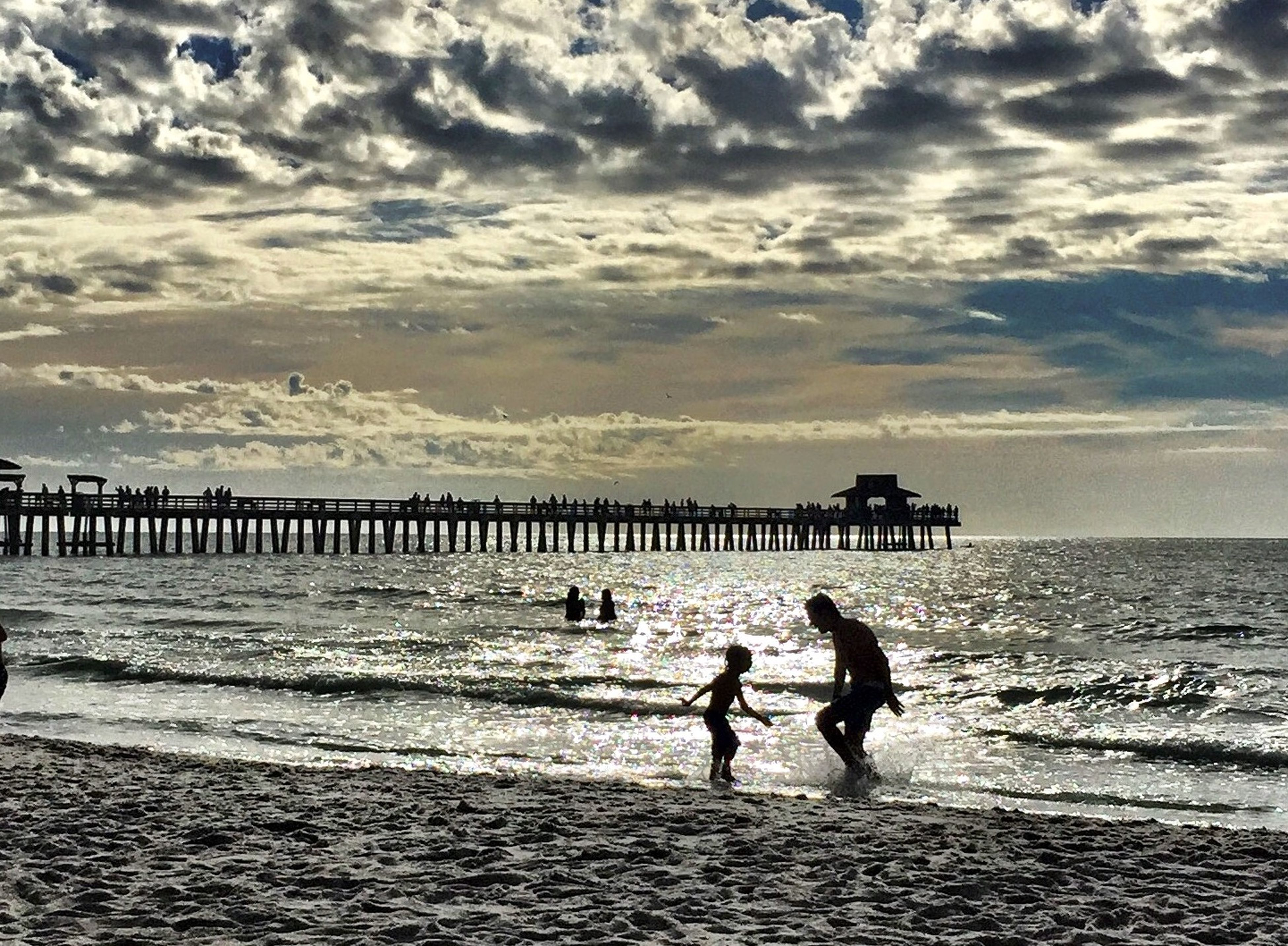 sea, water, beach, horizon over water, sky, lifestyles, leisure activity, men, shore, cloud - sky, sand, full length, silhouette, pier, person, scenics, vacations, tranquil scene