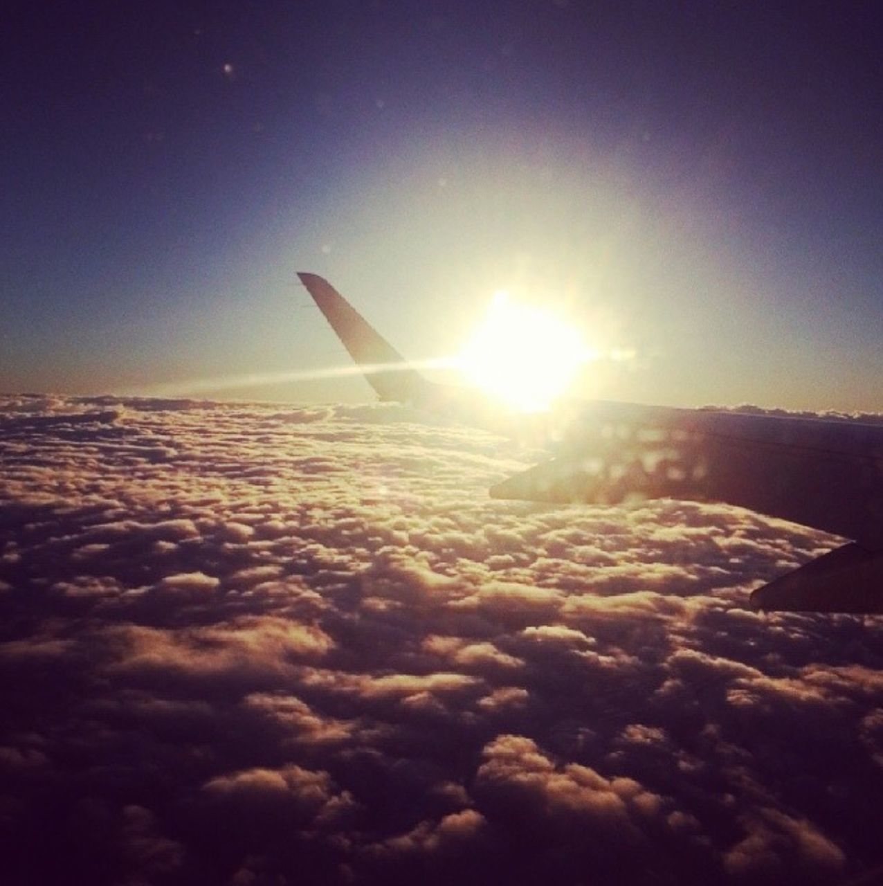 nature, sky, sun, beauty in nature, airplane, majestic, scenics, airplane wing, aerial view, sunbeam, sunset, lens flare, outdoors, transportation, journey, cloud - sky, no people, tranquility, flying, travel, sunlight, blue, tranquil scene, sky only, day, the natural world