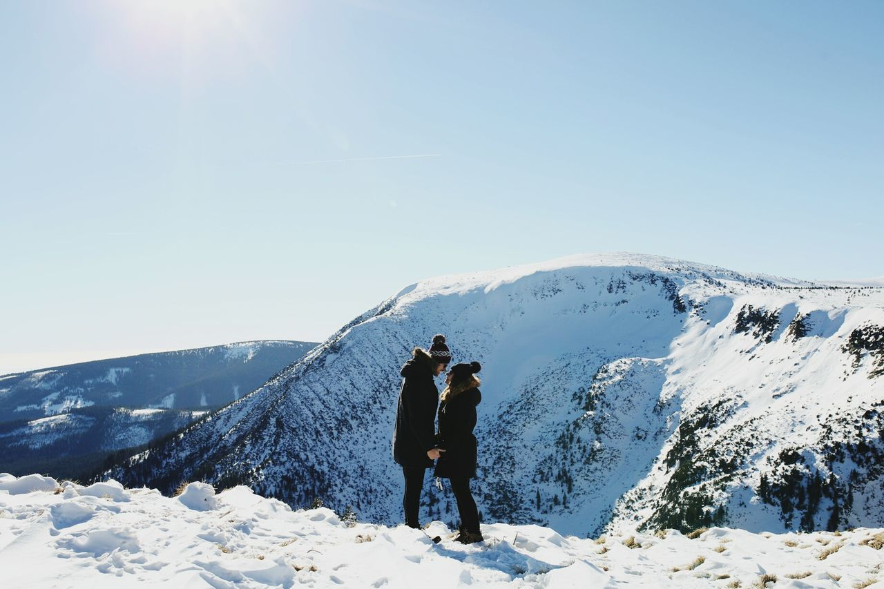 winter, snow, cold temperature, real people, mountain, two people, weather, nature, leisure activity, rear view, sunlight, beauty in nature, lifestyles, togetherness, full length, day, scenics, outdoors, tranquil scene, adventure, snowcapped mountain, sky, vacations, men, standing, clear sky, tranquility, people
