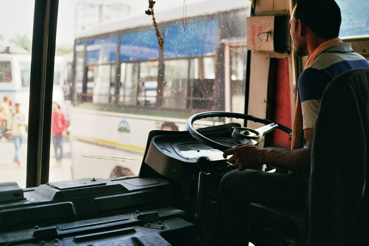 transportation, real people, vehicle interior, mode of transport, land vehicle, one person, window, steering wheel, sitting, train - vehicle, public transportation, day, men, occupation, vehicle seat, technology, human hand, indoors, young adult, people