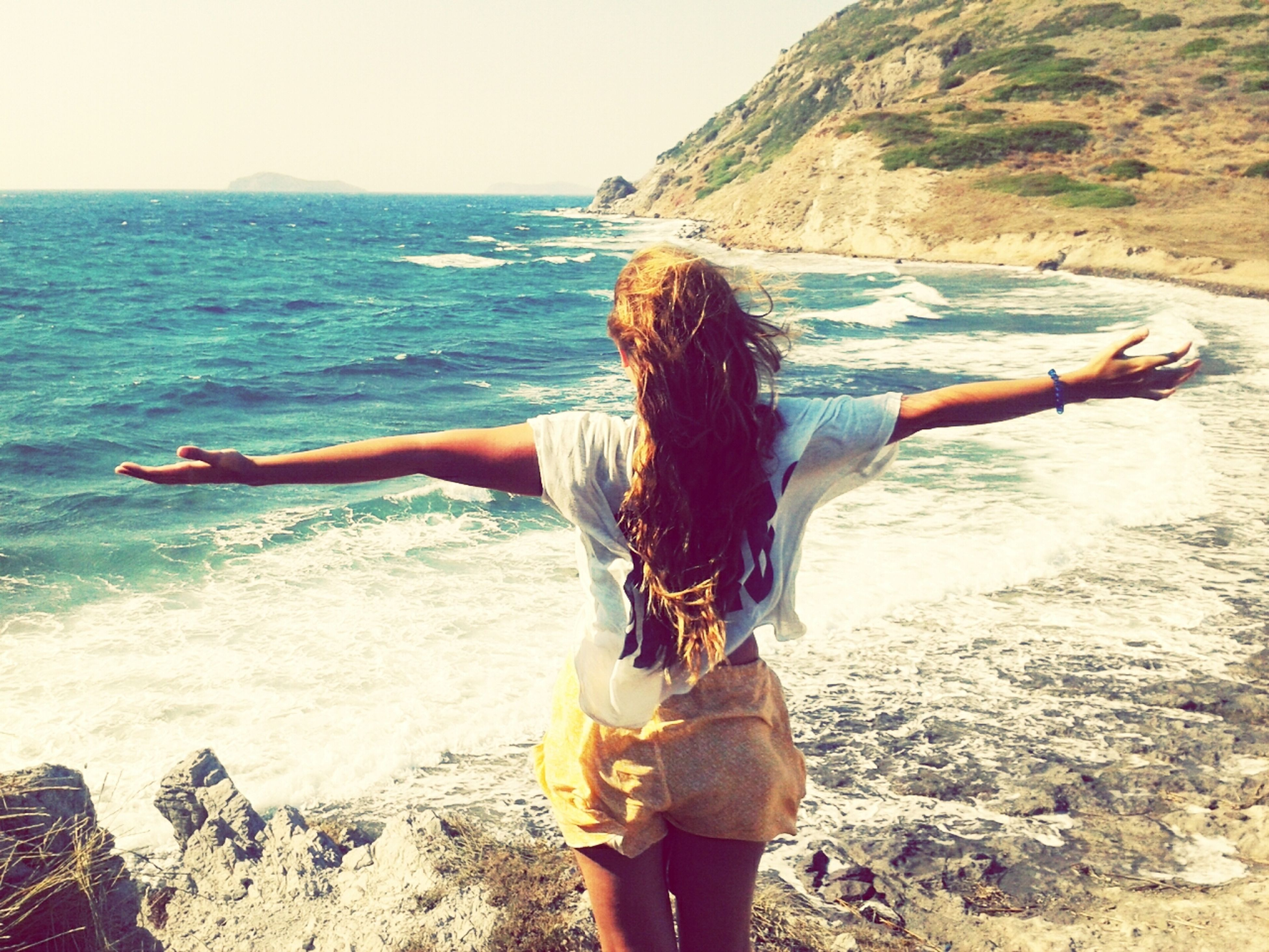 lifestyles, sea, long hair, beach, leisure activity, young women, water, young adult, shore, standing, casual clothing, vacations, person, full length, horizon over water, rear view