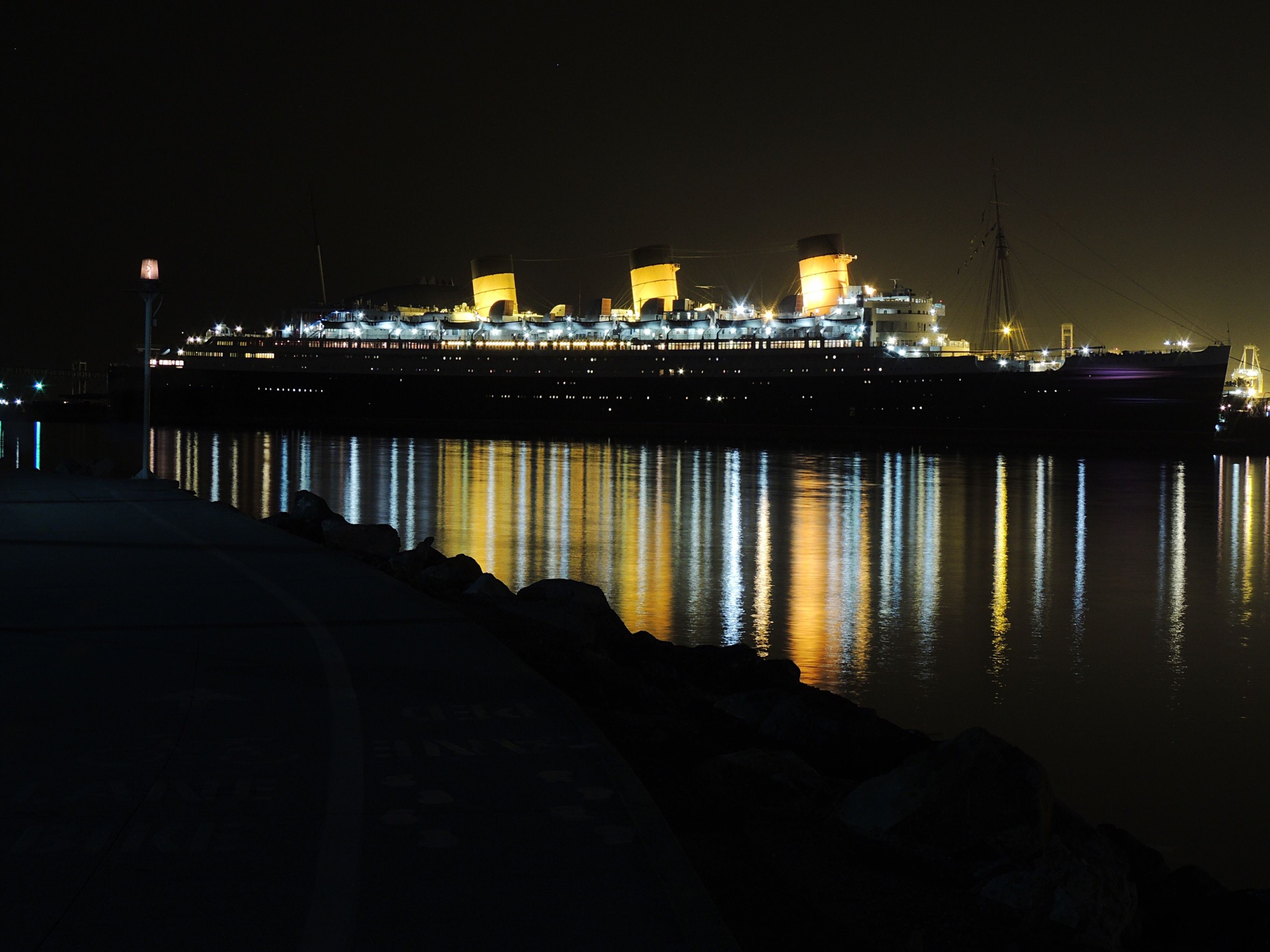 water, illuminated, night, built structure, river, architecture, reflection, sea, city, building exterior, street light, pier, waterfront, transportation, bridge - man made structure, sky, clear sky, connection, lighting equipment, dark