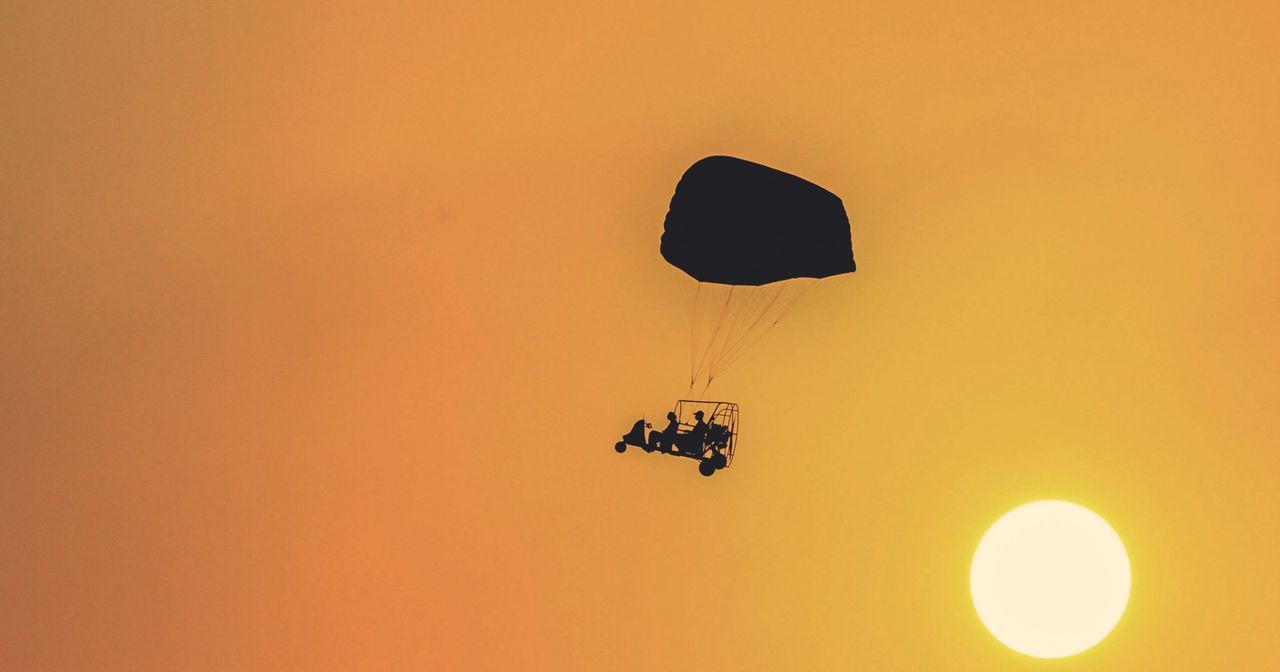 sunset, real people, orange color, low angle view, adventure, leisure activity, silhouette, transportation, lifestyles, nature, mode of transport, outdoors, extreme sports, mid-air, one person, flying, parachute, sky, beauty in nature, men, clear sky, paragliding, day, people