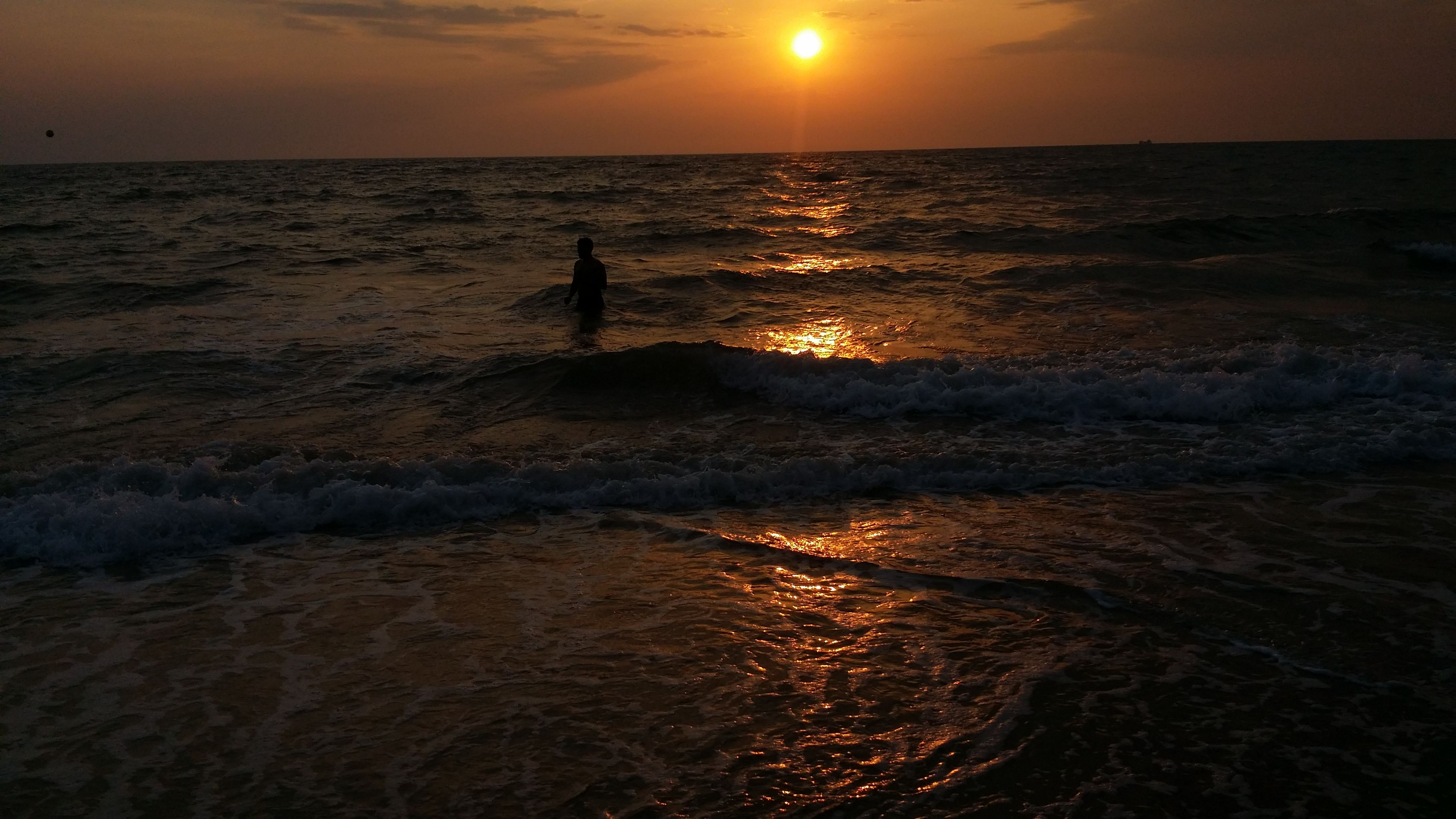 sea, sunset, water, horizon over water, silhouette, sun, scenics, tranquil scene, beach, beauty in nature, tranquility, shore, nature, idyllic, orange color, sky, reflection, sunlight, rippled, wave