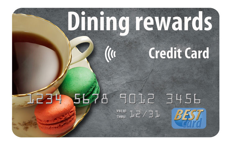 A dining rewards credit card is illustrated here. Tea and macrons are on the card. Photo illustration. Isolated. Rewards Textured  Card Credit Credit Card Cute Dining Rewards Car Dining Table Isolated On White Macro Saucer