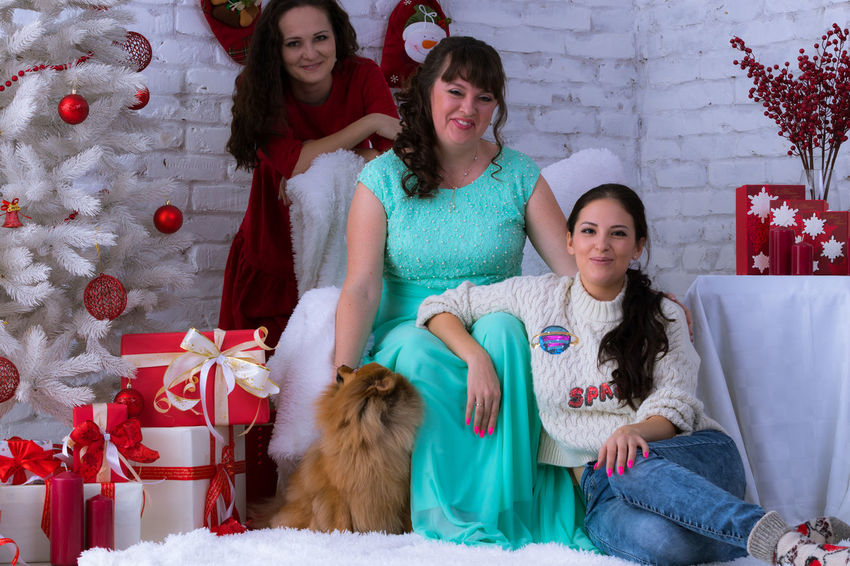 Christmas Holiday - Event Celebration Christmas Present Gift Young Women Sitting Christmas Tree Young Adult Togetherness Enjoyment Happiness Cheerful Elégance EyeEm Selects Christmas Spirit Christmas Eve Christmas Time Christmas Party Beautiful Woman Looking At Camera Anticipation Christmas Friendship Dog❤