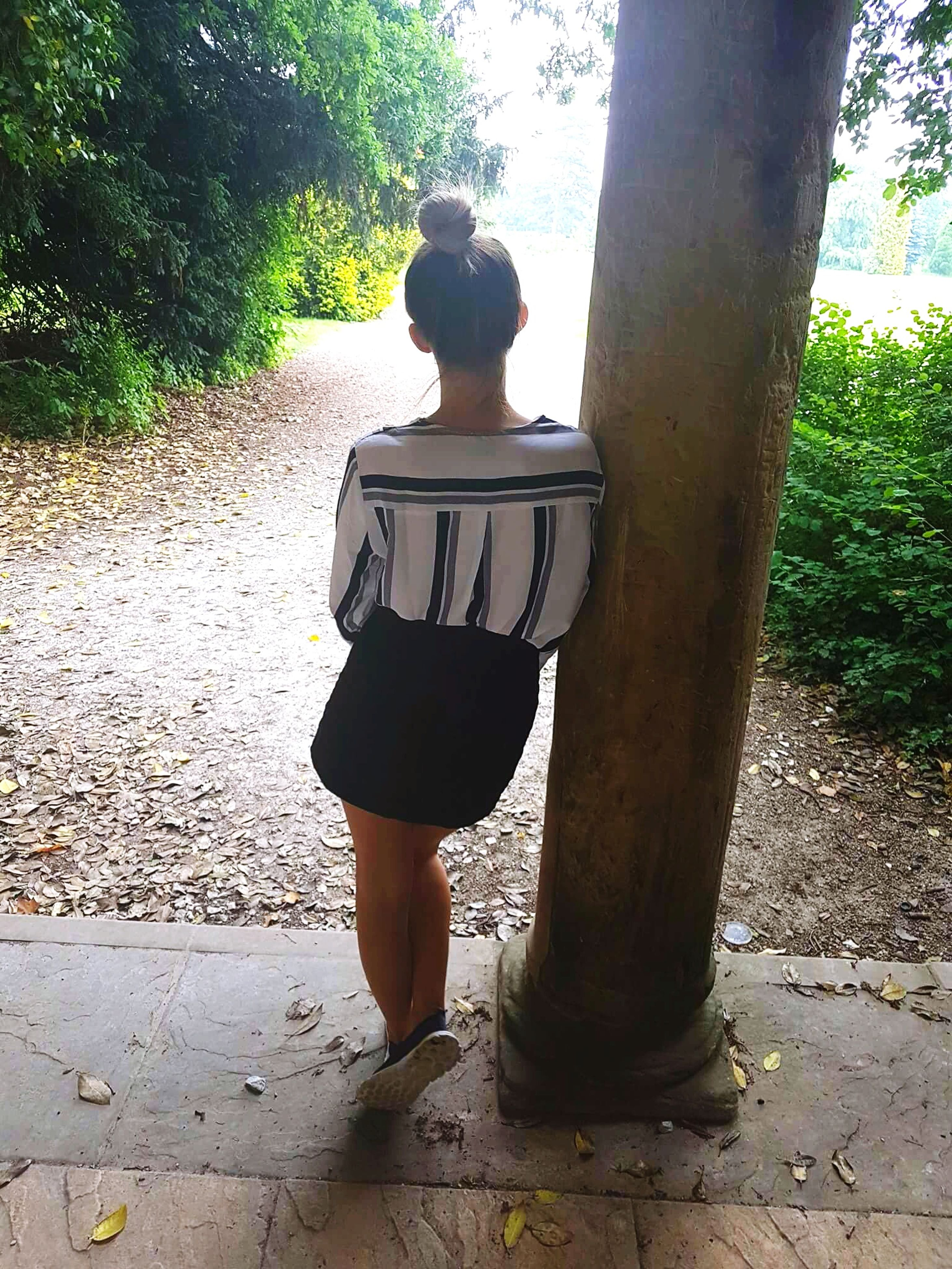 tree, real people, one person, rear view, standing, day, full length, tree trunk, leisure activity, lifestyles, casual clothing, growth, outdoors, nature, women, young adult, people