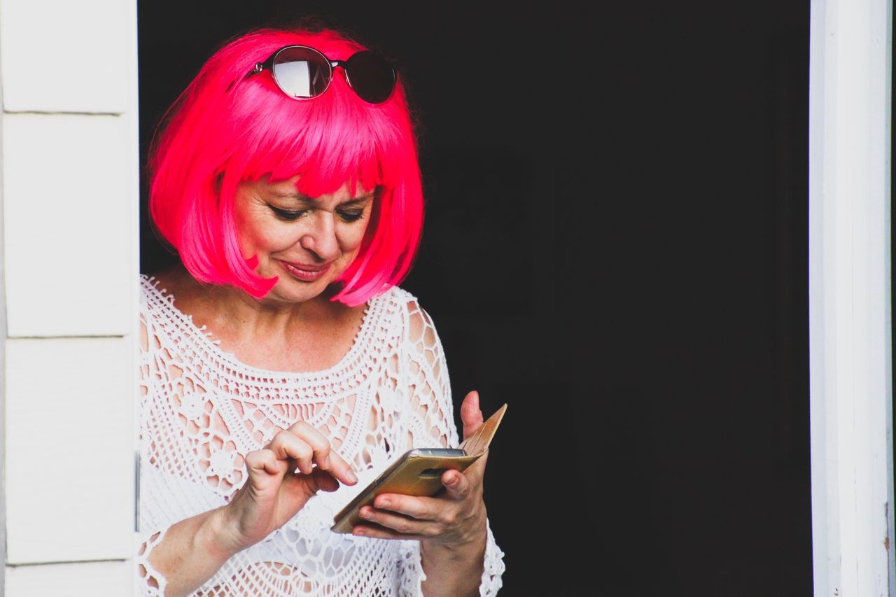 Woman in pink wig and sunglasses using a mobile phone Communication Holding Lifestyles Wireless Technology Real People One Person Technology Indoors  People Adult Wig Pink Wig Mobile Phone Mobile Devices Woman Portrait My Year My View