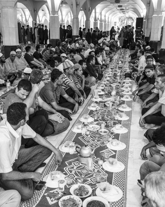 Men sitting in long rows in front of food waiting to break fast (iftar) Black & White Bnw Breaking Fast Fasting Food Food And Drink Iftar Indoors  Islam Large Group Of People Men Mosque Muslims Ramadan  Ramadan Kareem Sitting The Photojournalist - 2017 EyeEm Awards