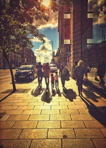 a family walking on sidewalk in city Street City Sidewalk Architecture City Life Walking Outdoors Sunlight Men Building Exterior Pedestrian Built_Structure People Day Sky Adult Adults Only Children Walking Walking Around Sunset Leeds Leeds, UK United Kingdom Let's Go. Together.