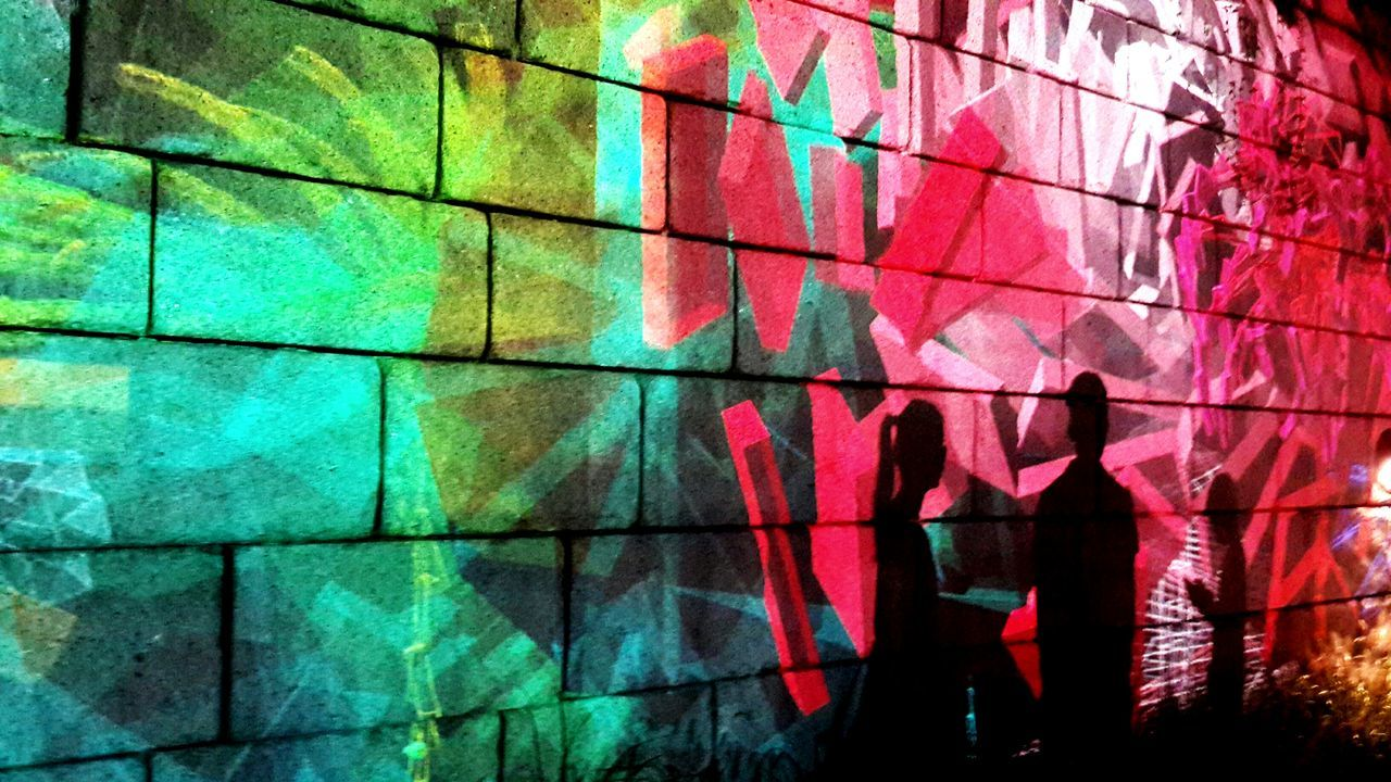graffiti, multi colored, real people, outdoors, lifestyles, shadow, one person, red, night, architecture, illuminated, building exterior, pixelated, people