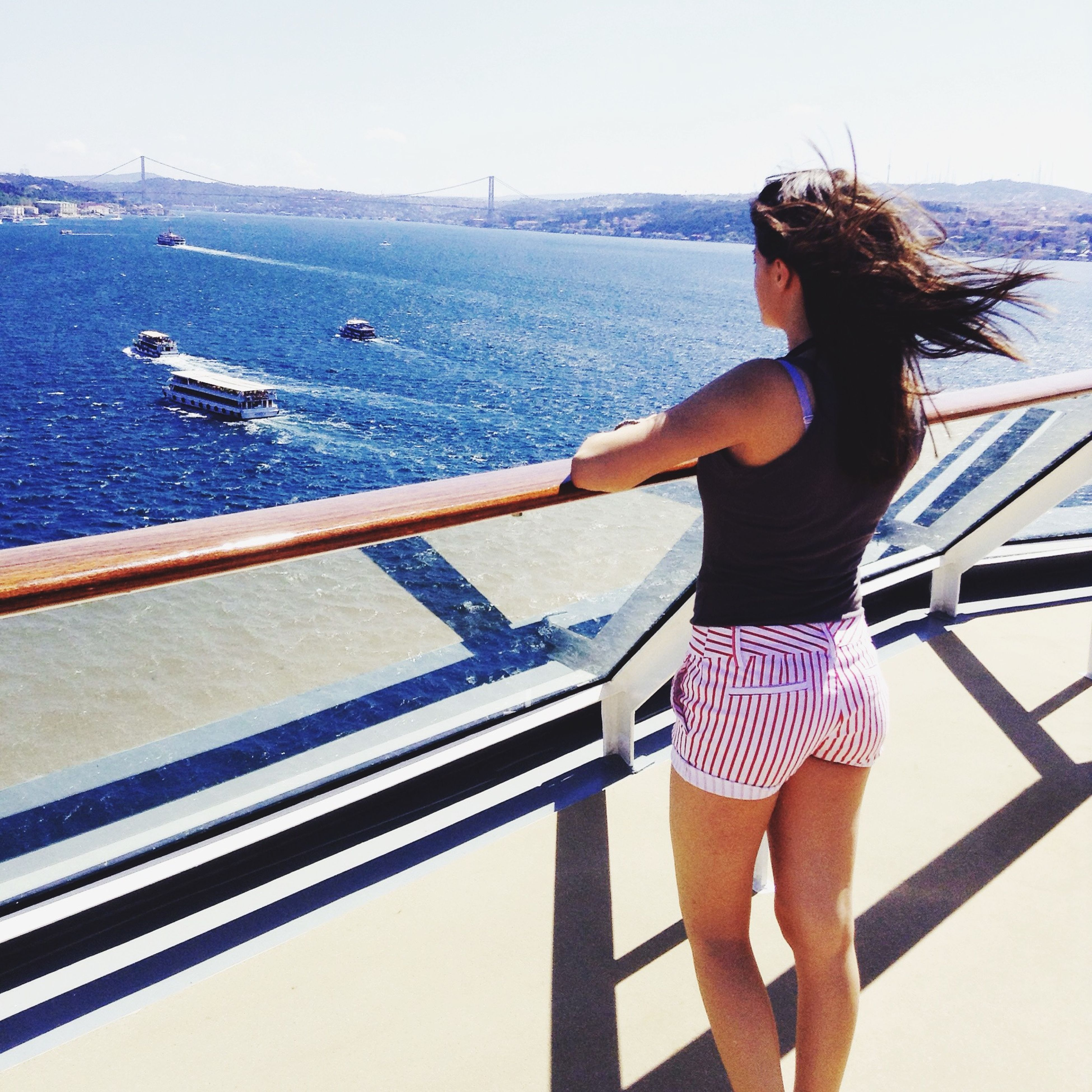 sea, lifestyles, water, railing, leisure activity, standing, young adult, full length, clear sky, casual clothing, rear view, three quarter length, young women, nautical vessel, person, sky, transportation, side view