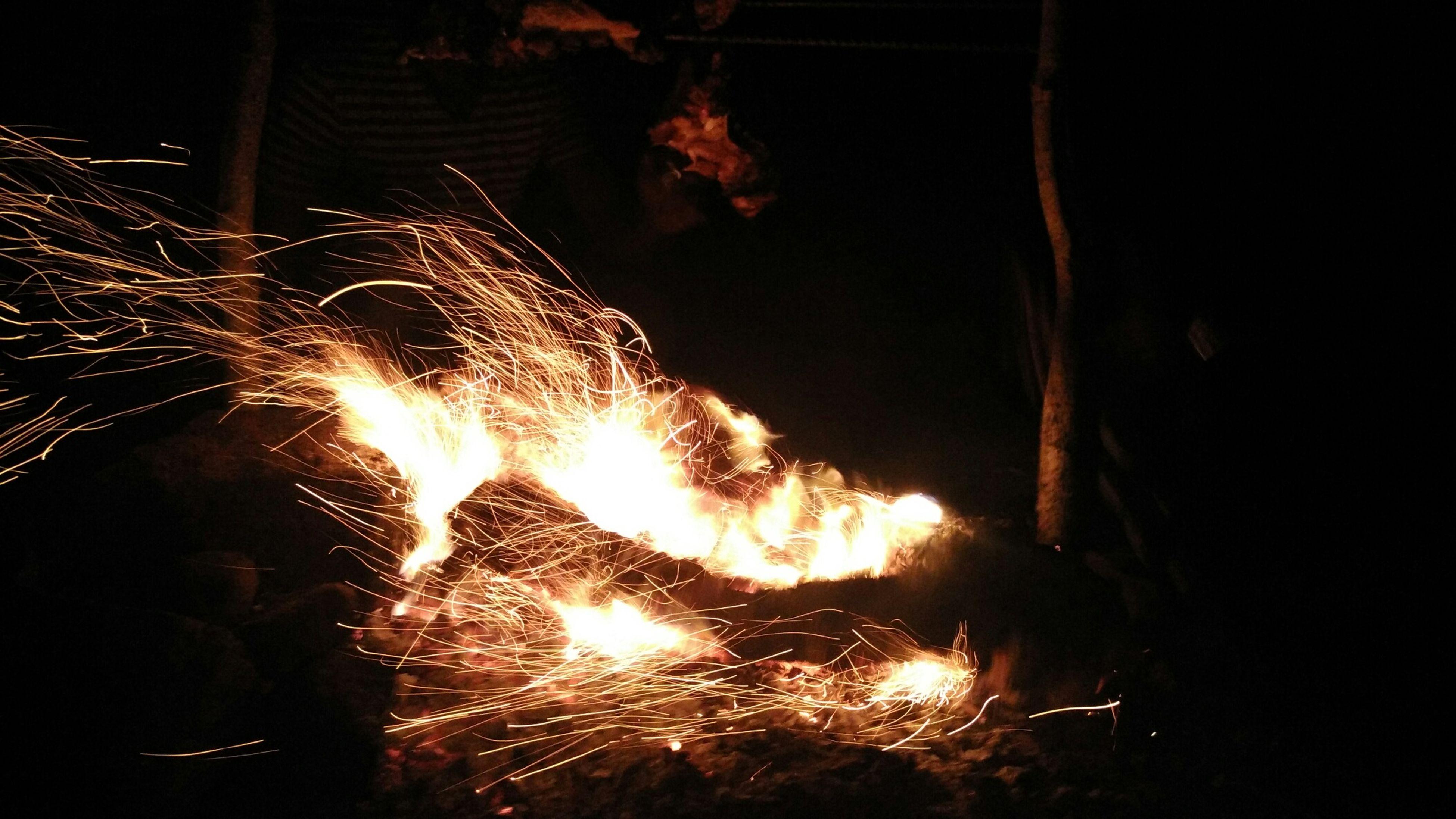 illuminated, night, glowing, fire - natural phenomenon, celebration, long exposure, lighting equipment, firework display, burning, sparks, exploding, flame, light - natural phenomenon, low angle view, motion, dark, light, lit, decoration, firework - man made object