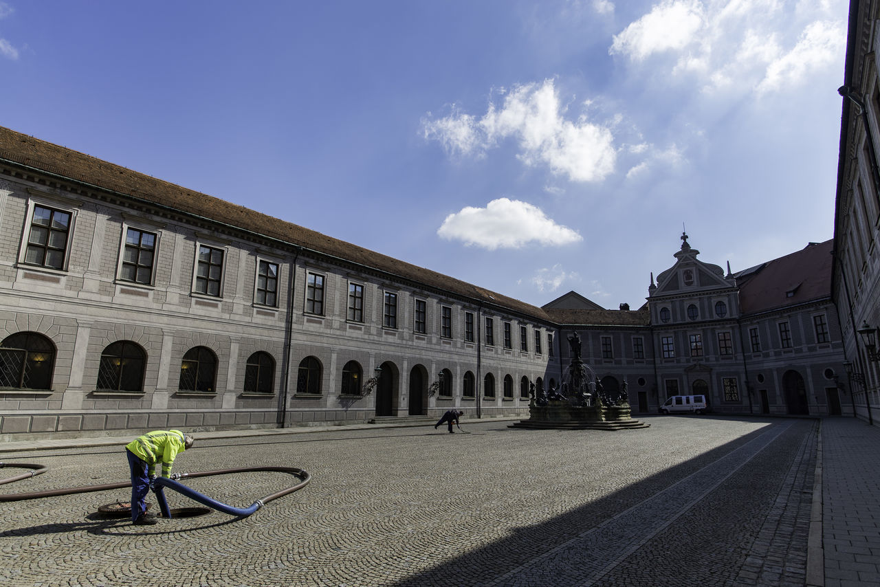 Cleaner Working At Manhole In Front Of Historic Building Against Sky