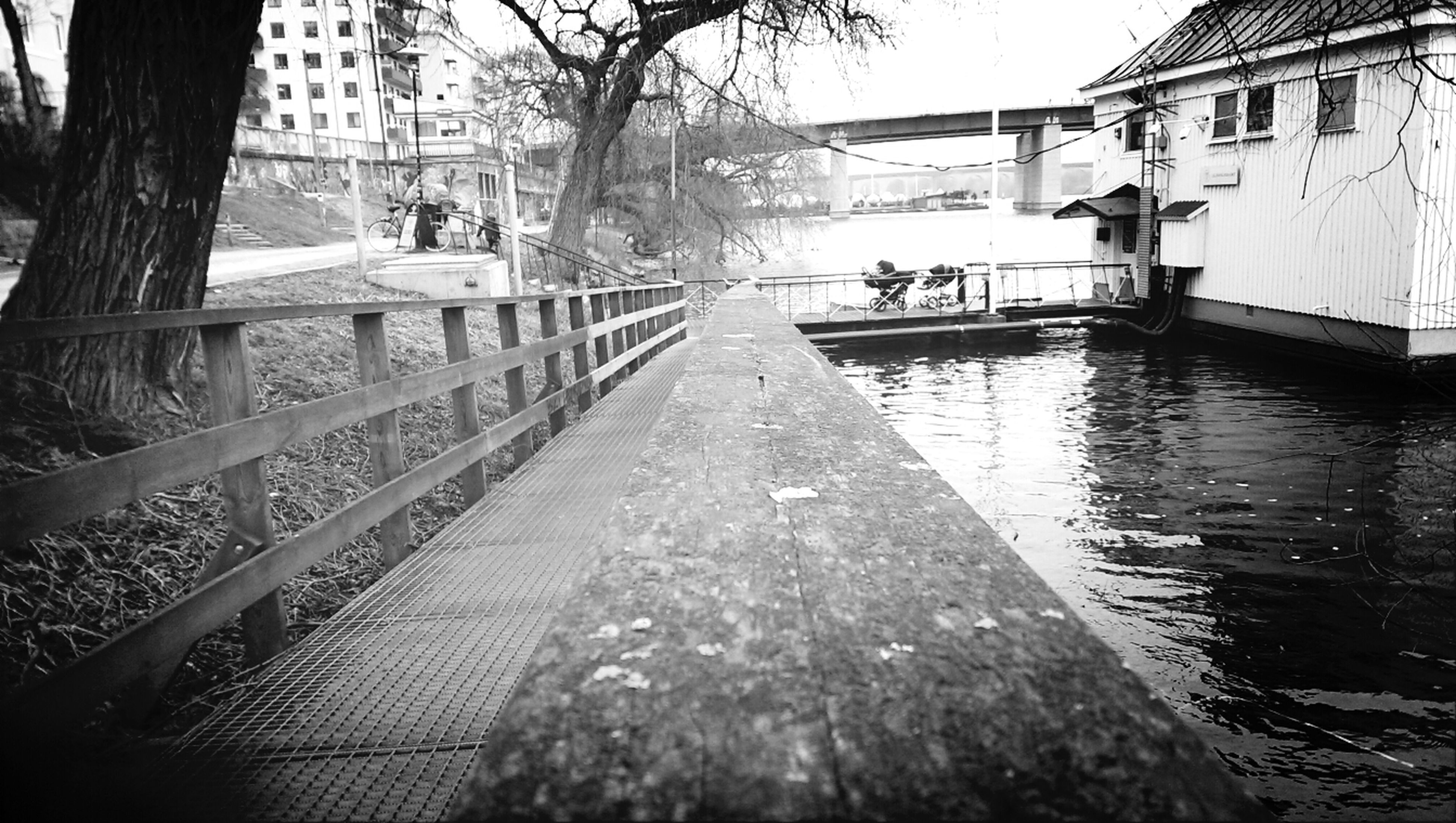 architecture, built structure, building exterior, water, the way forward, diminishing perspective, tree, canal, railing, city, vanishing point, connection, footbridge, incidental people, bridge - man made structure, day, outdoors, transportation, river, residential building