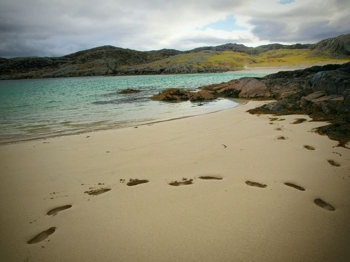 Beach Footprints Sand Sea Landscape Outdoors Water Sky Clouds Lost My Way Going Nowhere Walking In Circles No People Beauty In Nature Coastal Feature Achmelvich Scotland Coastline Rocks Hills Blue Water The Great Outdoors - 2017 EyeEm Awards Tranquil Scene Hillside Tranquility
