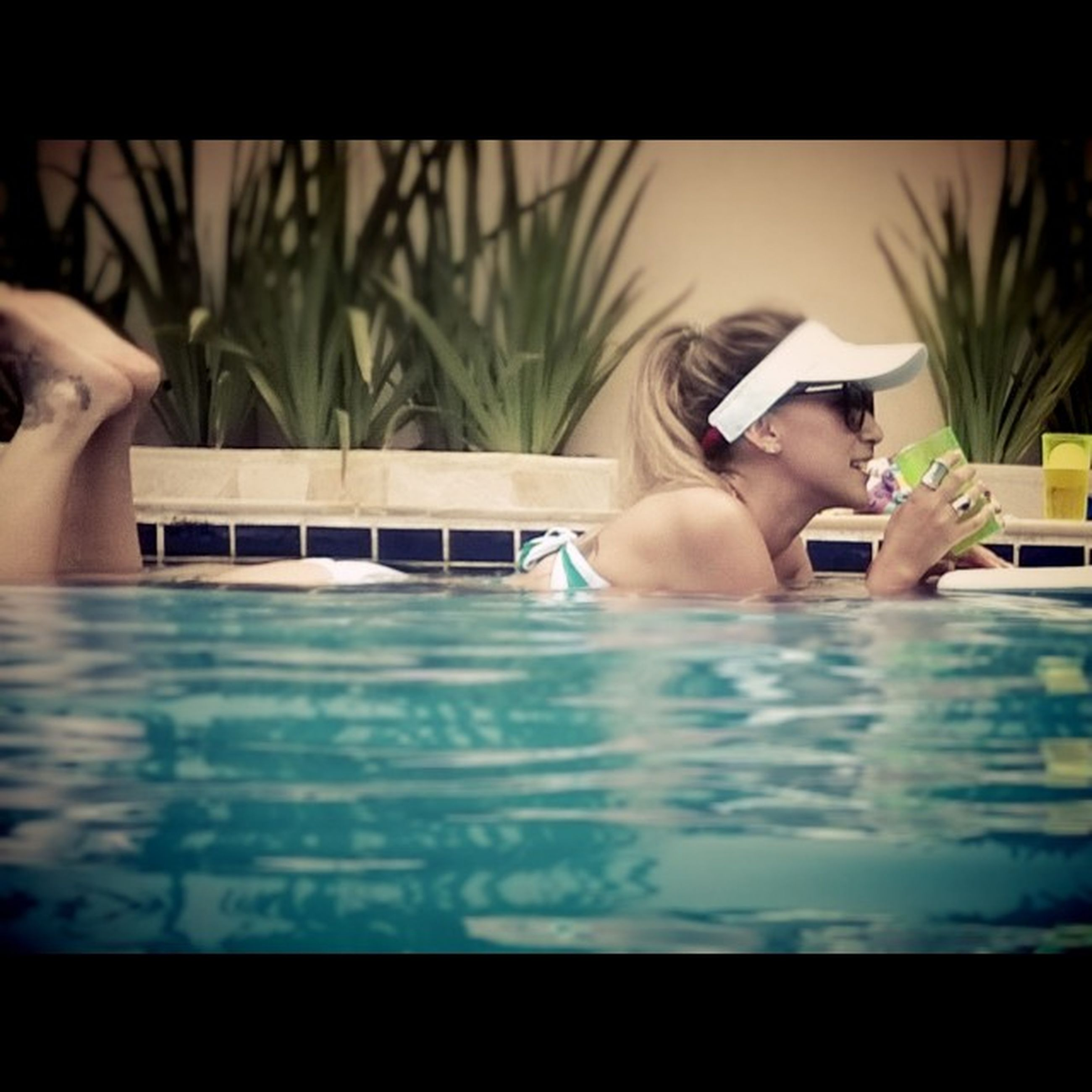lifestyles, leisure activity, indoors, young adult, young women, person, long hair, holding, water, sitting, side view, auto post production filter, wireless technology, sensuality, relaxation, swimming pool