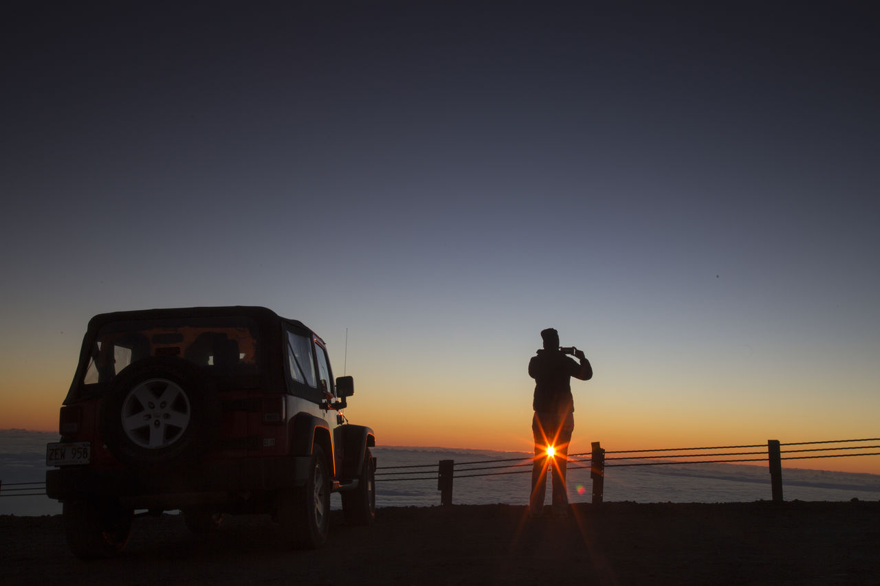 sunset, transportation, real people, mode of transport, men, silhouette, copy space, nature, clear sky, sea, rear view, standing, land vehicle, sky, one person, full length, outdoors, sun, beach, lifestyles, leisure activity, sand, day, people