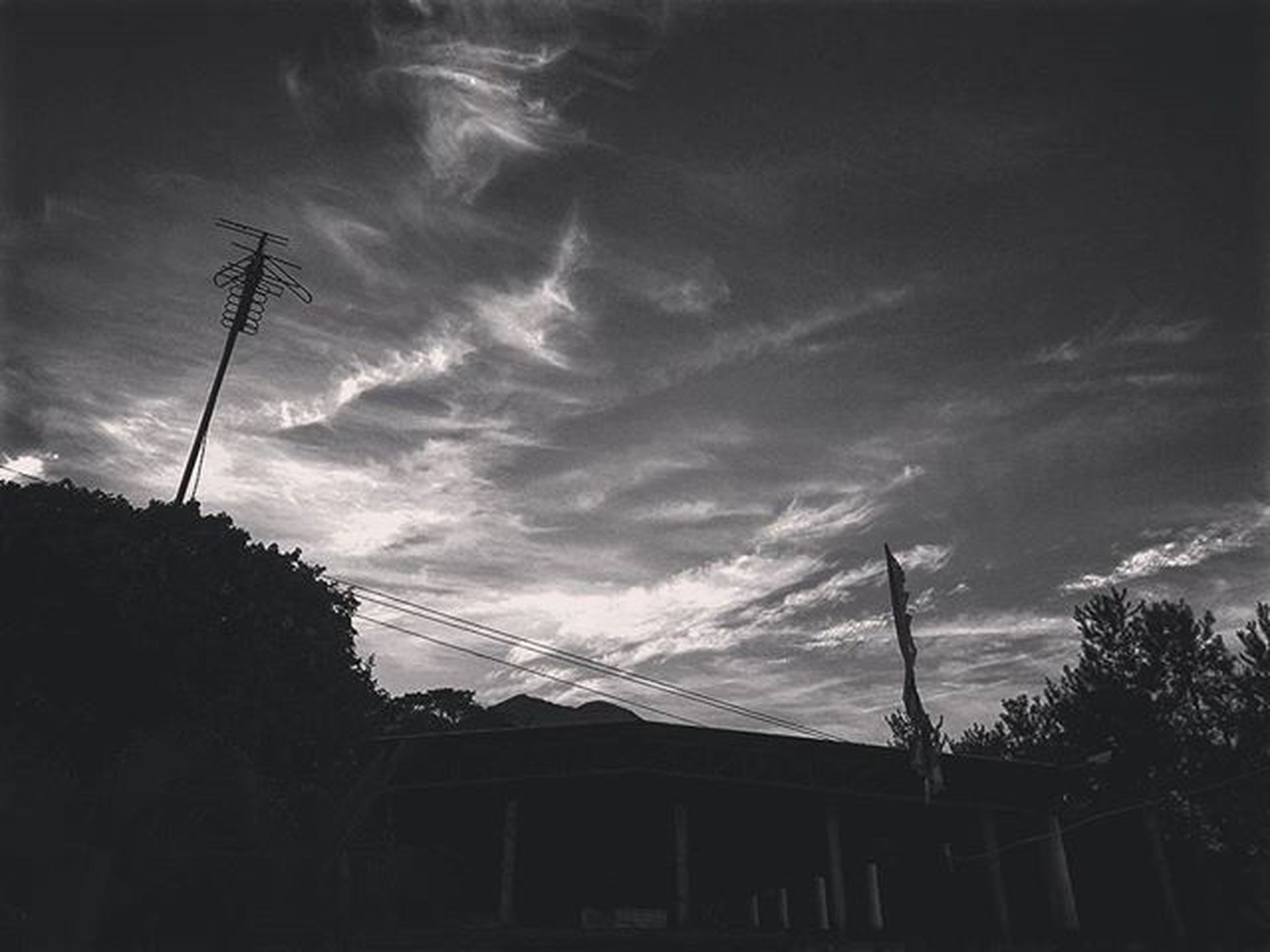 sky, low angle view, power line, electricity pylon, cloud - sky, electricity, cable, built structure, cloudy, power supply, building exterior, architecture, connection, silhouette, house, fuel and power generation, tree, cloud, technology, nature