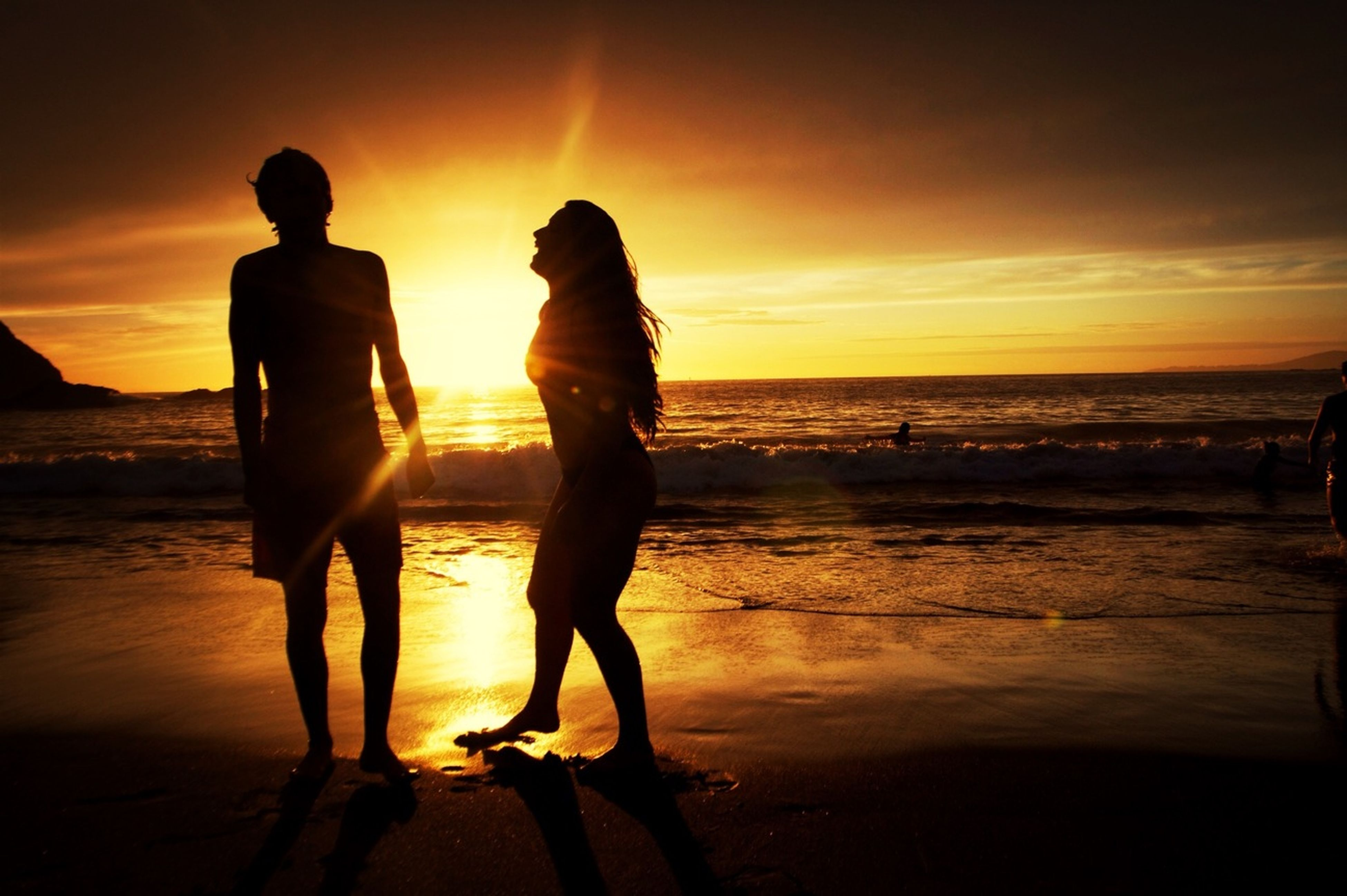 sunset, sea, beach, horizon over water, shore, water, sun, silhouette, orange color, lifestyles, sky, leisure activity, standing, scenics, beauty in nature, full length, person, sand, vacations