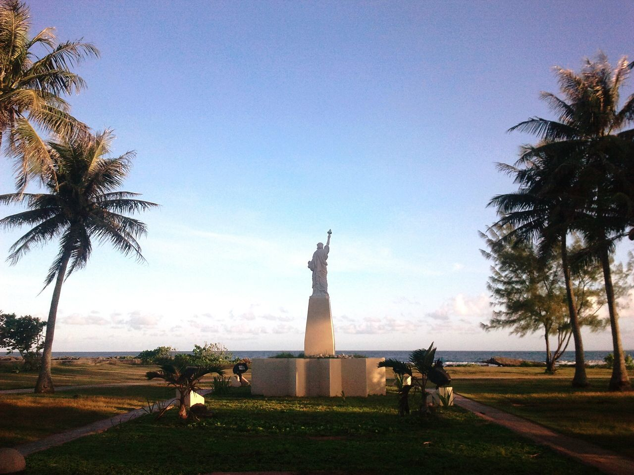 statue, human representation, sculpture, female likeness, tree, palm tree, travel destinations, sky, water, monument, travel, tourism, growth, day, outdoors, no people, nature, beauty in nature