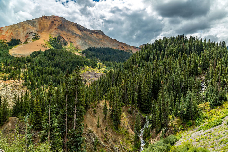 The San Juan Skyway forms a 233 mile loop in southwest Colorado traversing the heart of the San Juan Mountains festuring breathtaking mountain views and includes the portion of US 550 between Silverton and Ouray known as the Million Dollar Highway. Agriculture Beauty In Nature Cloud - Sky Colorado Day Forest Green Color Landscape Million Dollar Highway Mountain Nature No People Outdoors Rockies Rocky Mountains San Juan Mountains San Juan Skyway Scenics Sky Southwest  Southwestern Usa Tree Waterfall