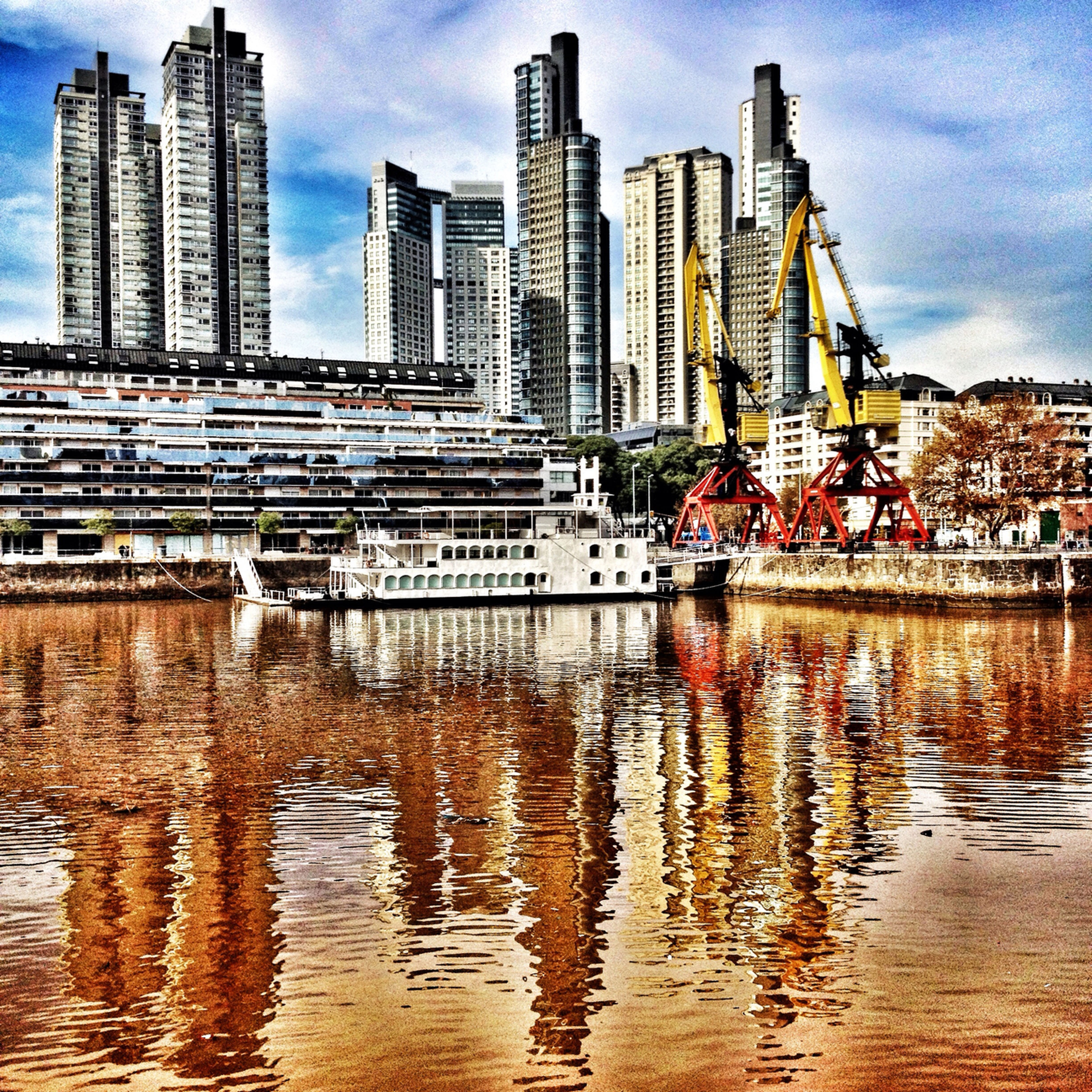 building exterior, architecture, built structure, water, city, waterfront, reflection, skyscraper, modern, building, sky, office building, river, cityscape, tall - high, tower, residential building, city life, urban skyline, residential structure