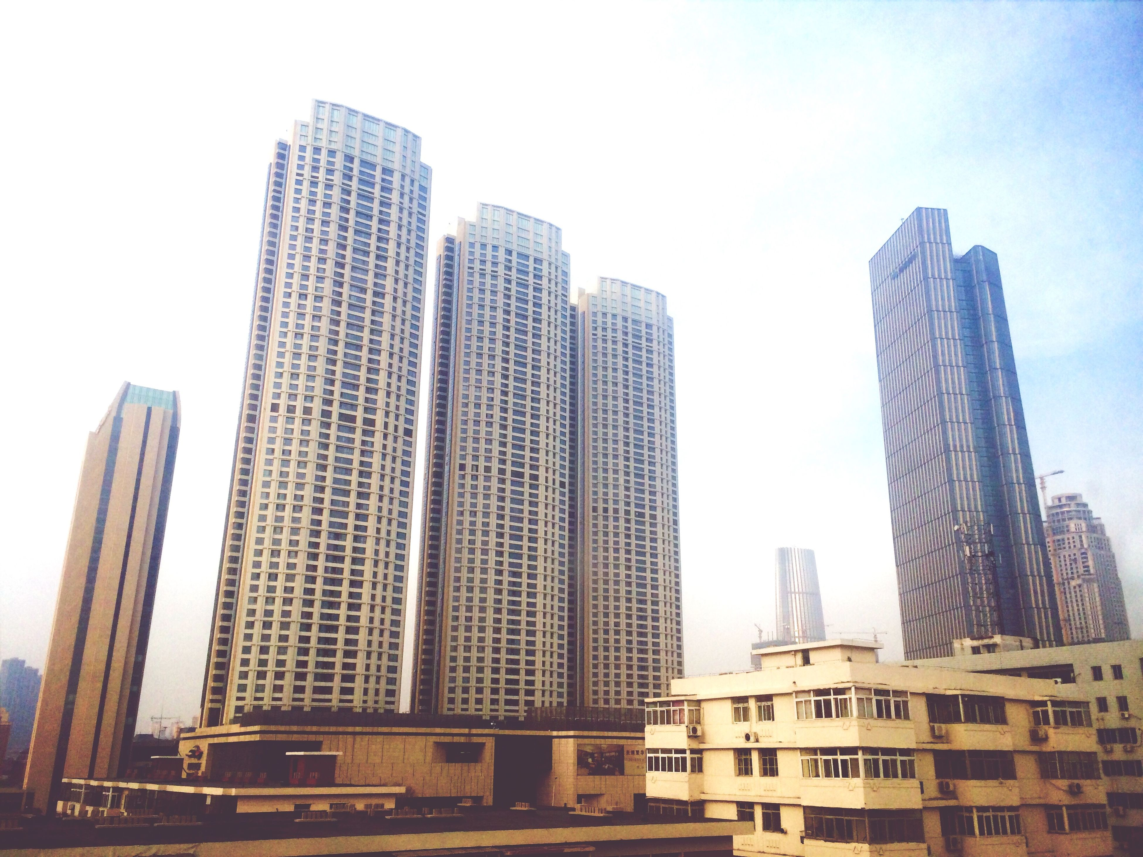 architecture, built structure, building exterior, skyscraper, city, tall - high, modern, office building, low angle view, tower, clear sky, development, sky, building, capital cities, tall, financial district, urban skyline, day, city life