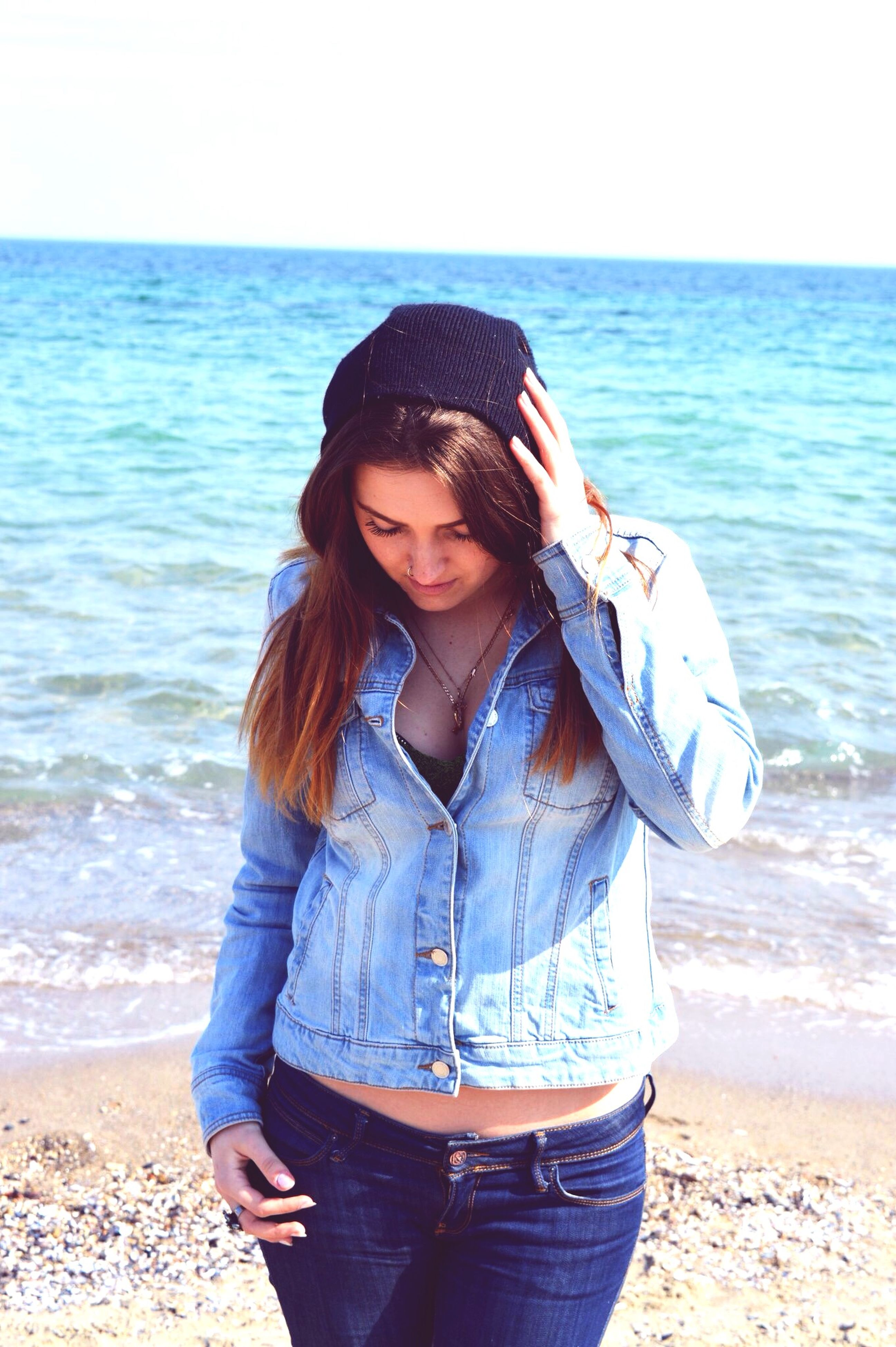 sea, beach, water, lifestyles, young adult, leisure activity, horizon over water, shore, casual clothing, person, standing, young women, sunglasses, sand, three quarter length, looking at camera, portrait, front view