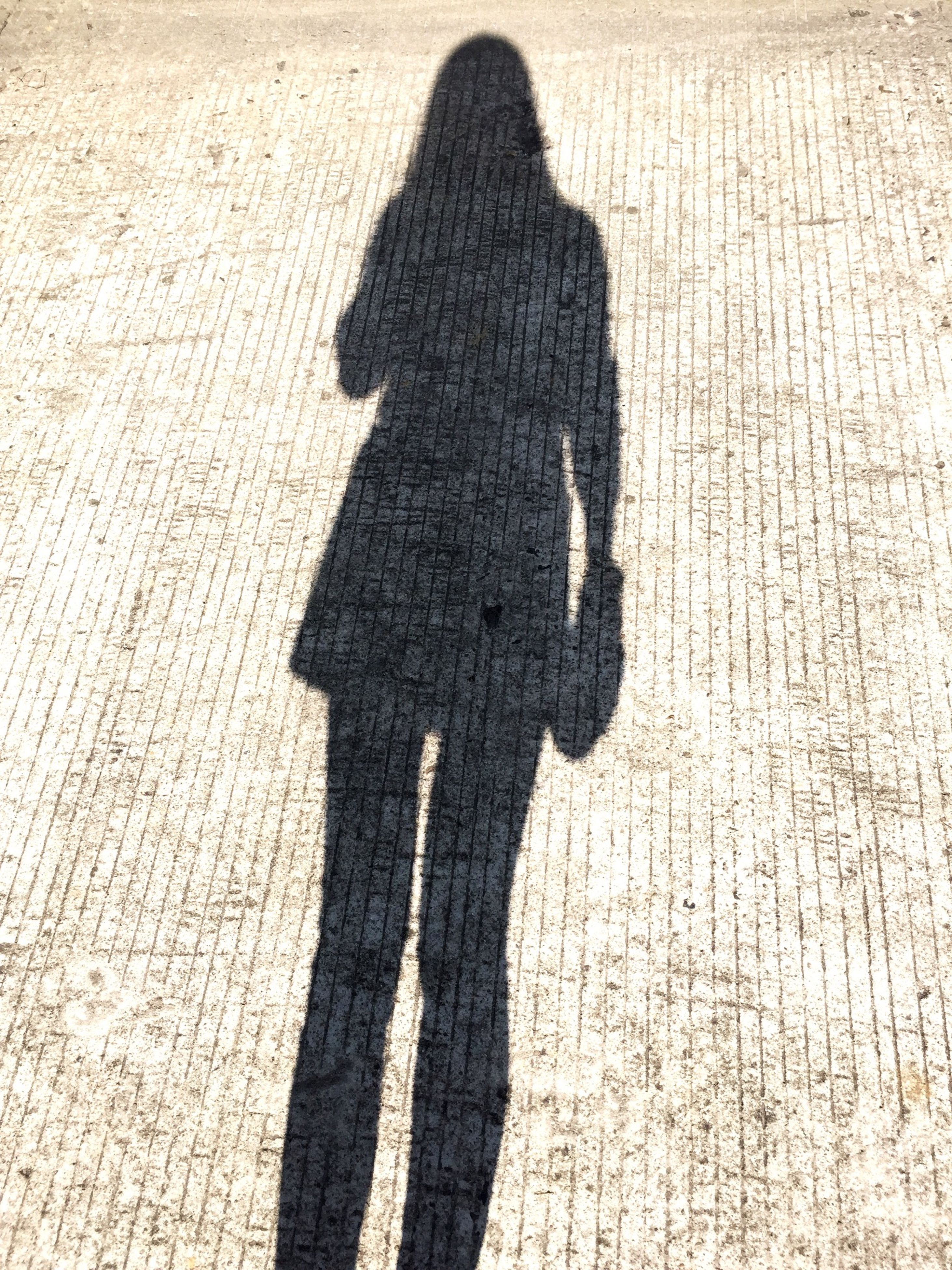 shadow, focus on shadow, human representation, sunlight, high angle view, outdoors, standing, day, silhouette, leisure activity, wall - building feature, art, three quarter length, sculpture, statue, lifestyles