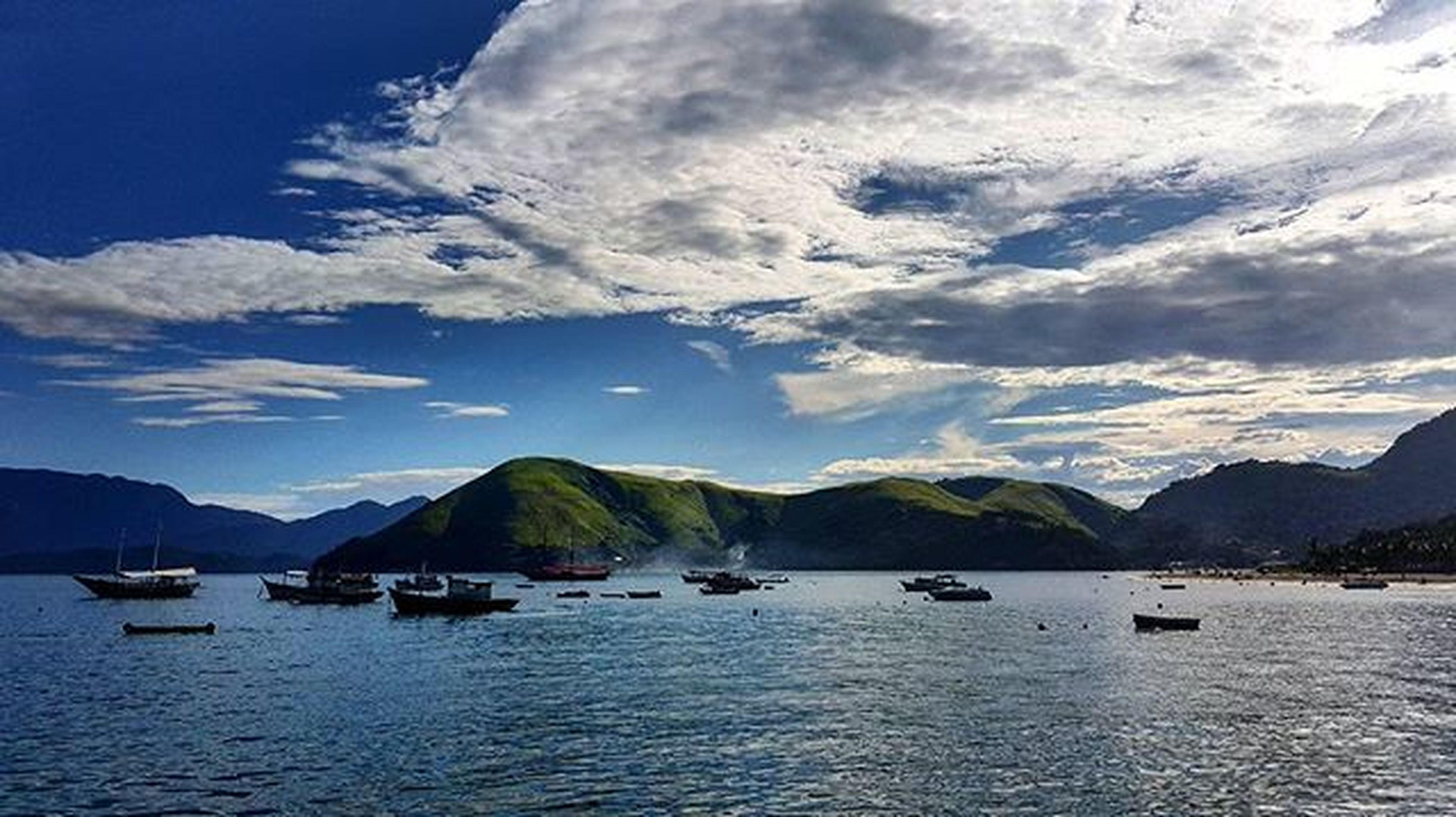 mountain, nautical vessel, water, transportation, mountain range, boat, mode of transport, sky, waterfront, scenics, sea, tranquil scene, tranquility, beauty in nature, cloud - sky, nature, cloud, moored, lake, cloudy