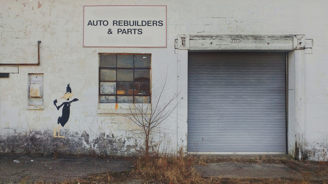 Building Exterior Built Structure Text Architecture Outdoors Day No People Close-up Cartoon Character Auto Repair Shop Auto Shop Garage Garage Doors Small Business Small Town Road Side