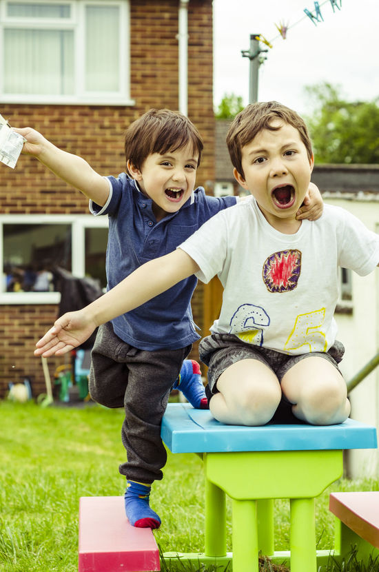 Two young brothers having fun, posing for the camera int he back garden. Arms Outstrected Back Garden Boy Boys Brothers Childhood Children Cute Enjoyment Fun Fun Garden Happy Open Mouth Outdoors Outside Picnic Table Playing Portrait Posing Shouting Young