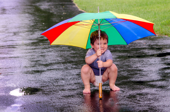 an active little boy happily splashes in a summertime rain with his colorful umbrella Kids Nature Active Active Children Barefoot Boy Child Childhood Day Driveway Enjoyment Full Length Fun Holding Lifestyles Male One Person Outdoors Playing In The Rain Real People Splashing Summer Umbrella Water Wet