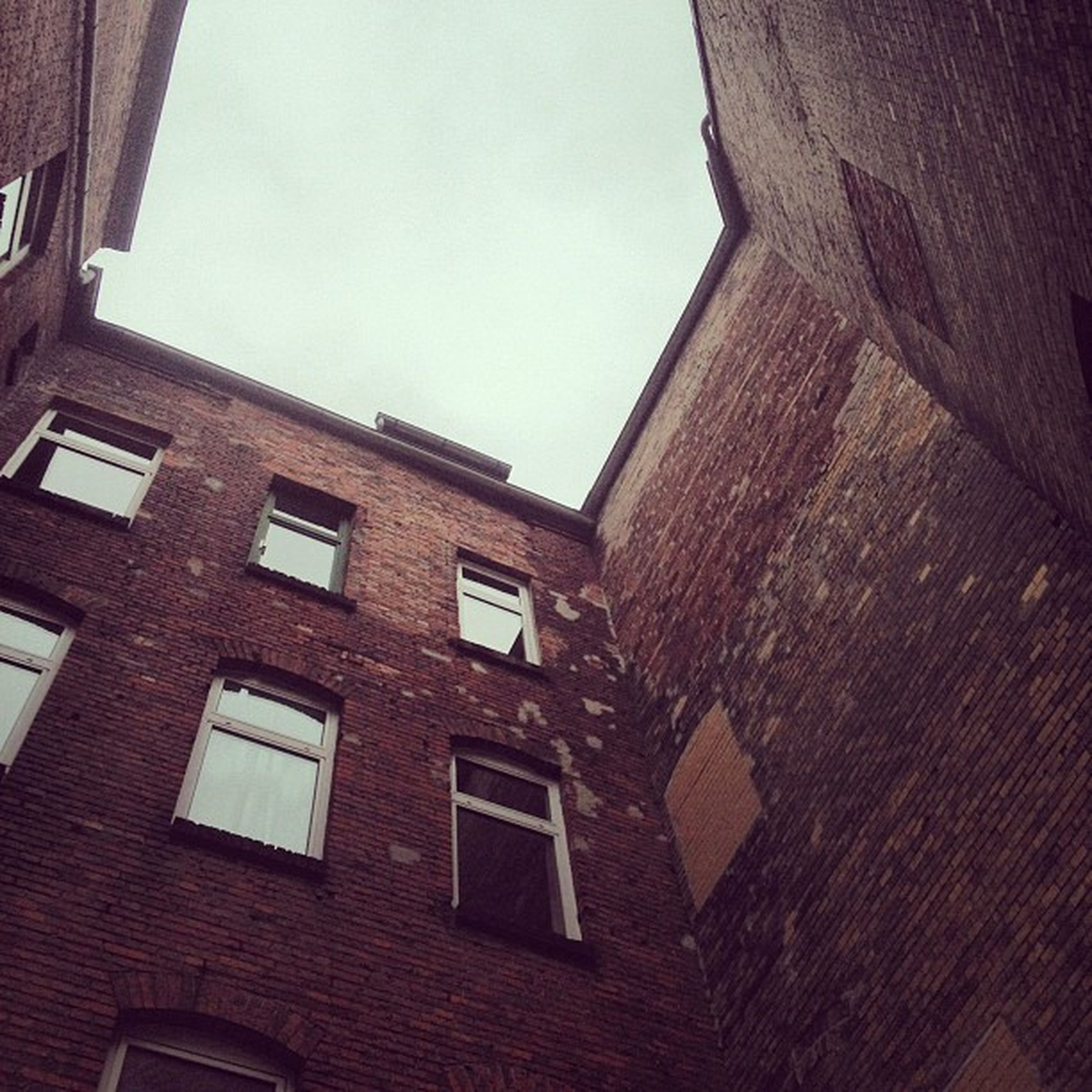 architecture, built structure, building exterior, low angle view, window, building, sky, brick wall, residential building, residential structure, day, wall - building feature, no people, outdoors, clear sky, old, city, arch, sunlight, wall
