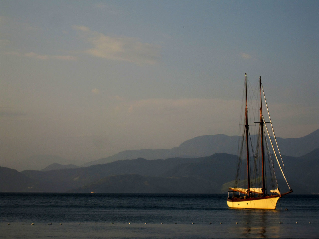 nautical vessel, sea, water, sky, mast, nature, scenics, sailboat, beauty in nature, transportation, tranquility, no people, outdoors, mode of transport, tranquil scene, sailing, mountain, moored, day, sailing ship