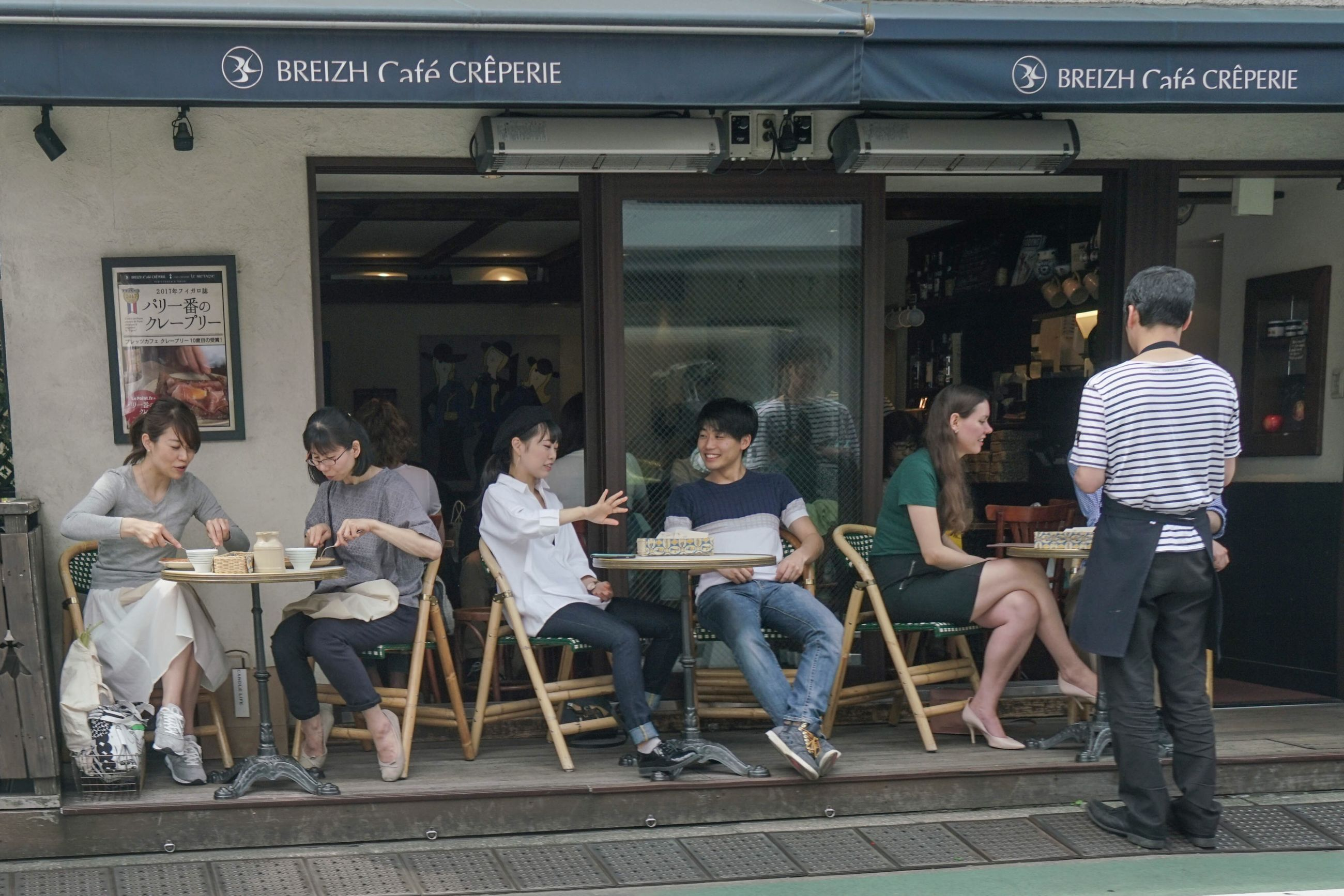 real people, sitting, full length, casual clothing, text, communication, chair, day, men, food and drink, standing, lifestyles, cafe, large group of people, women, indoors, food, architecture, young adult, people