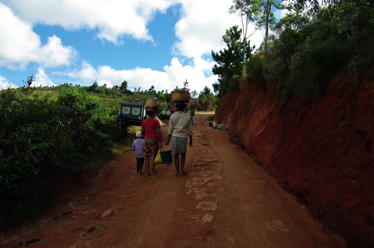 On the road to Saha Forest camp, I met a family going to the market, following this red path Adult Boys Child Day Full Length Hard Work Leisure Activity Local Landmark Local Population Madagascar  Men Nature Outdoors People Real People Rear View Sky The Way Forward Togetherness Tree Walking Women