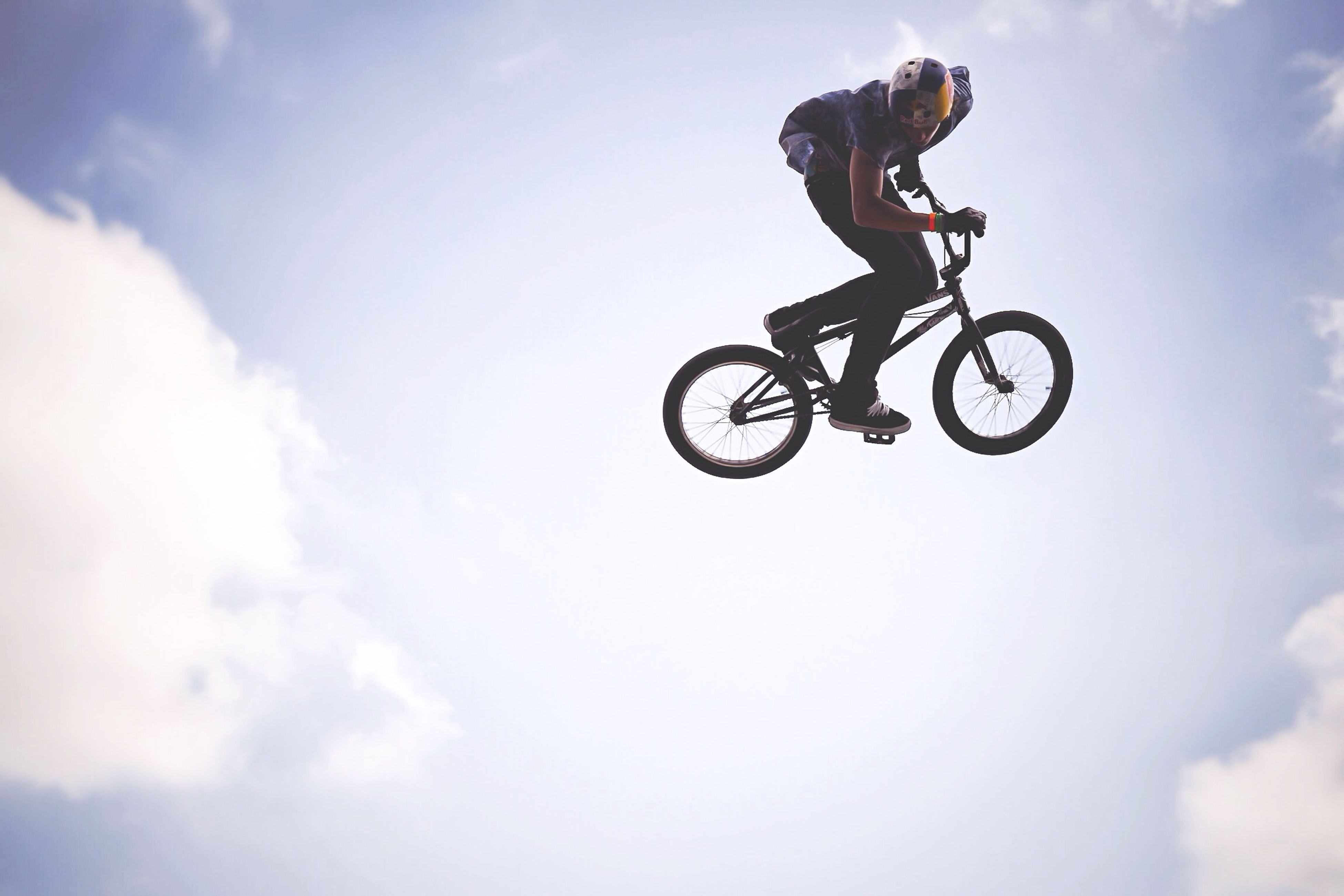 bicycle, sky, transportation, mid-air, extreme sports, sport, low angle view, leisure activity, stunt, mode of transport, cloud - sky, riding, lifestyles, cycling, adventure, full length, men, motion