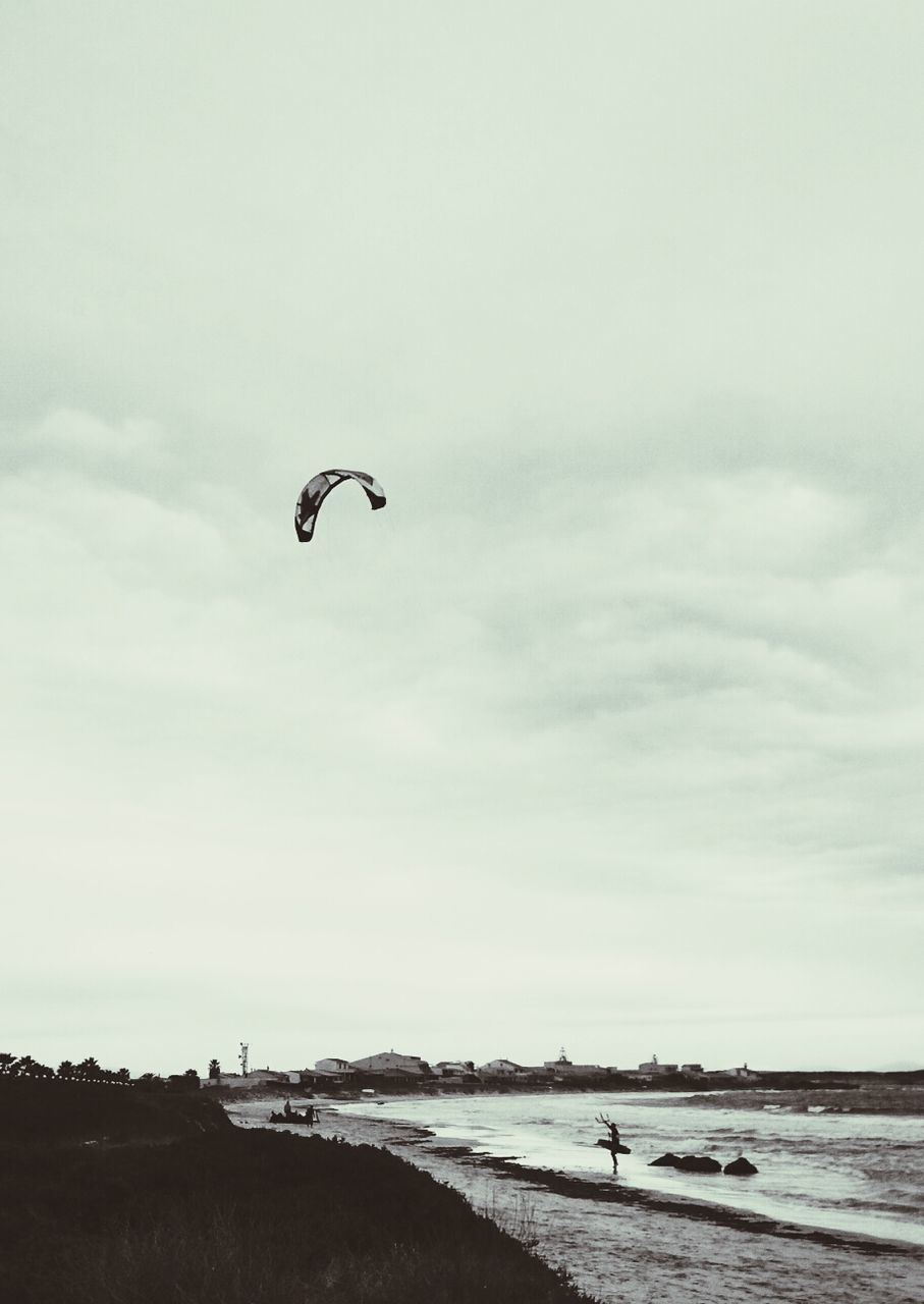 Person Paragliding On Beach By Sea Against Cloudy Sky