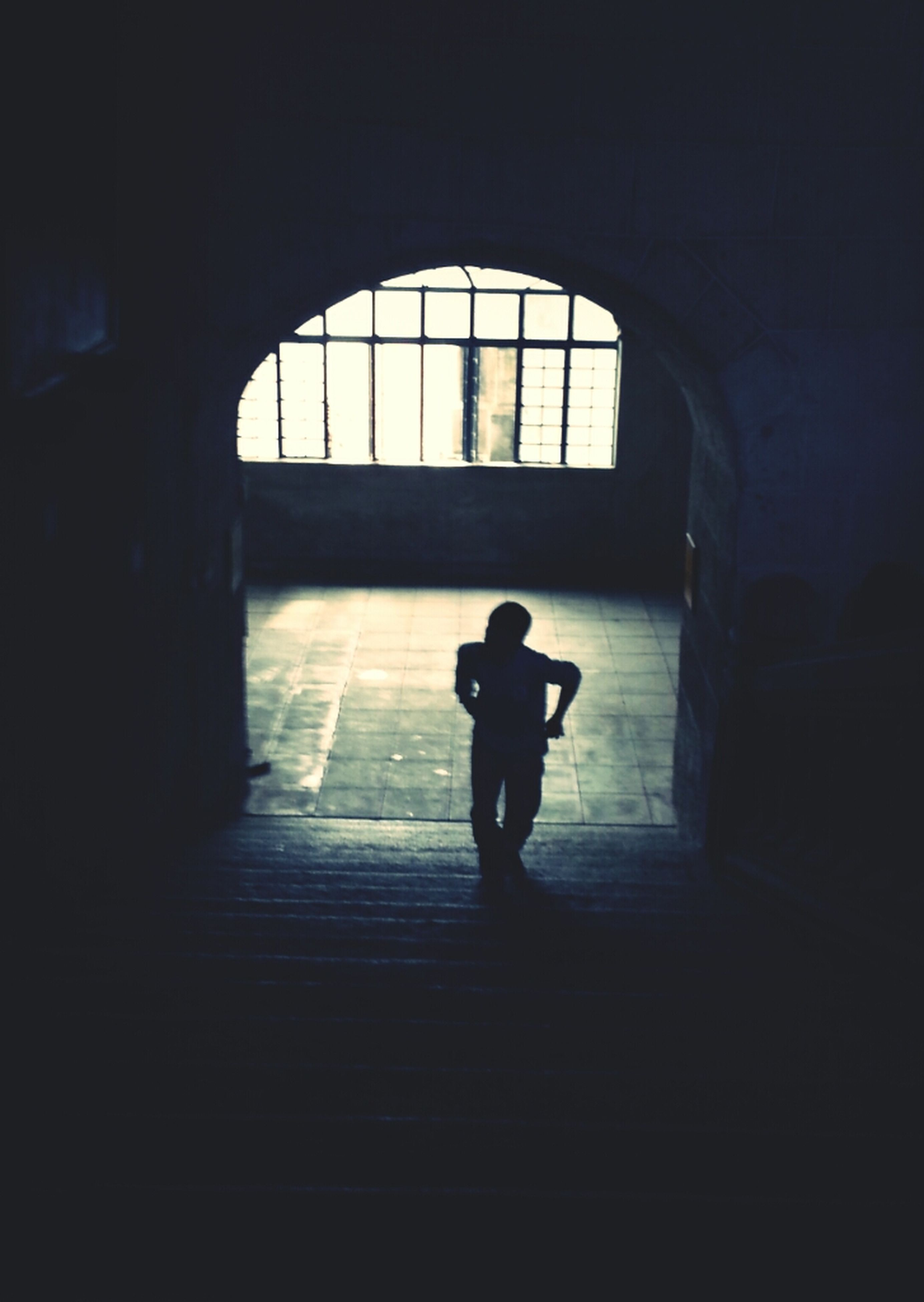 indoors, silhouette, full length, architecture, walking, built structure, lifestyles, men, tunnel, window, rear view, arch, standing, sunlight, leisure activity, dark, shadow, wall - building feature