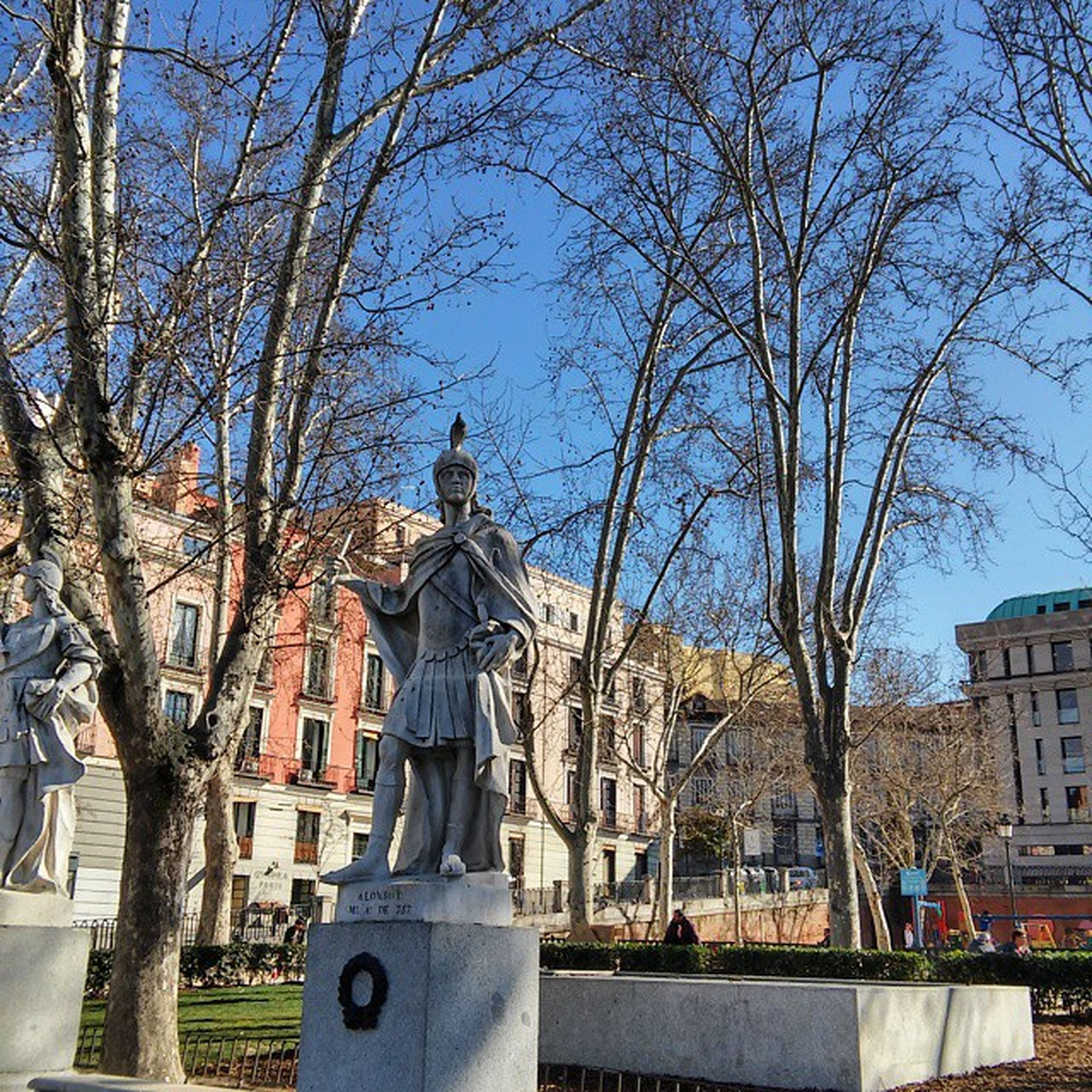 building exterior, architecture, built structure, bare tree, tree, sky, statue, city, sculpture, human representation, day, residential building, residential structure, sunlight, art and craft, outdoors, men, incidental people, blue
